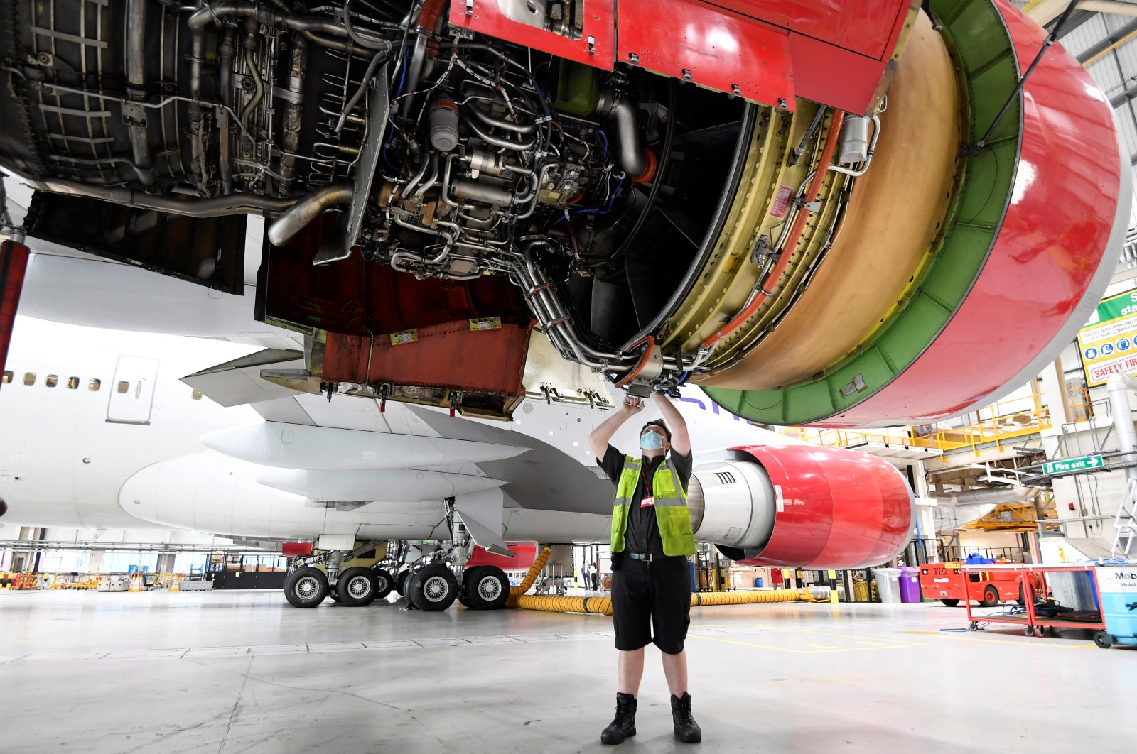 "An engineer works on the Boeing 747 jumbo G-VROY, named ""Pretty Woman,"" being retired from passenger service by Virgin Atlantic Airways, before its redeployment as freight and military carrier, in a maintenance hangar at Heathrow Airport, London, Britain, Dec. 11, 2020. (Reuters Photo)"