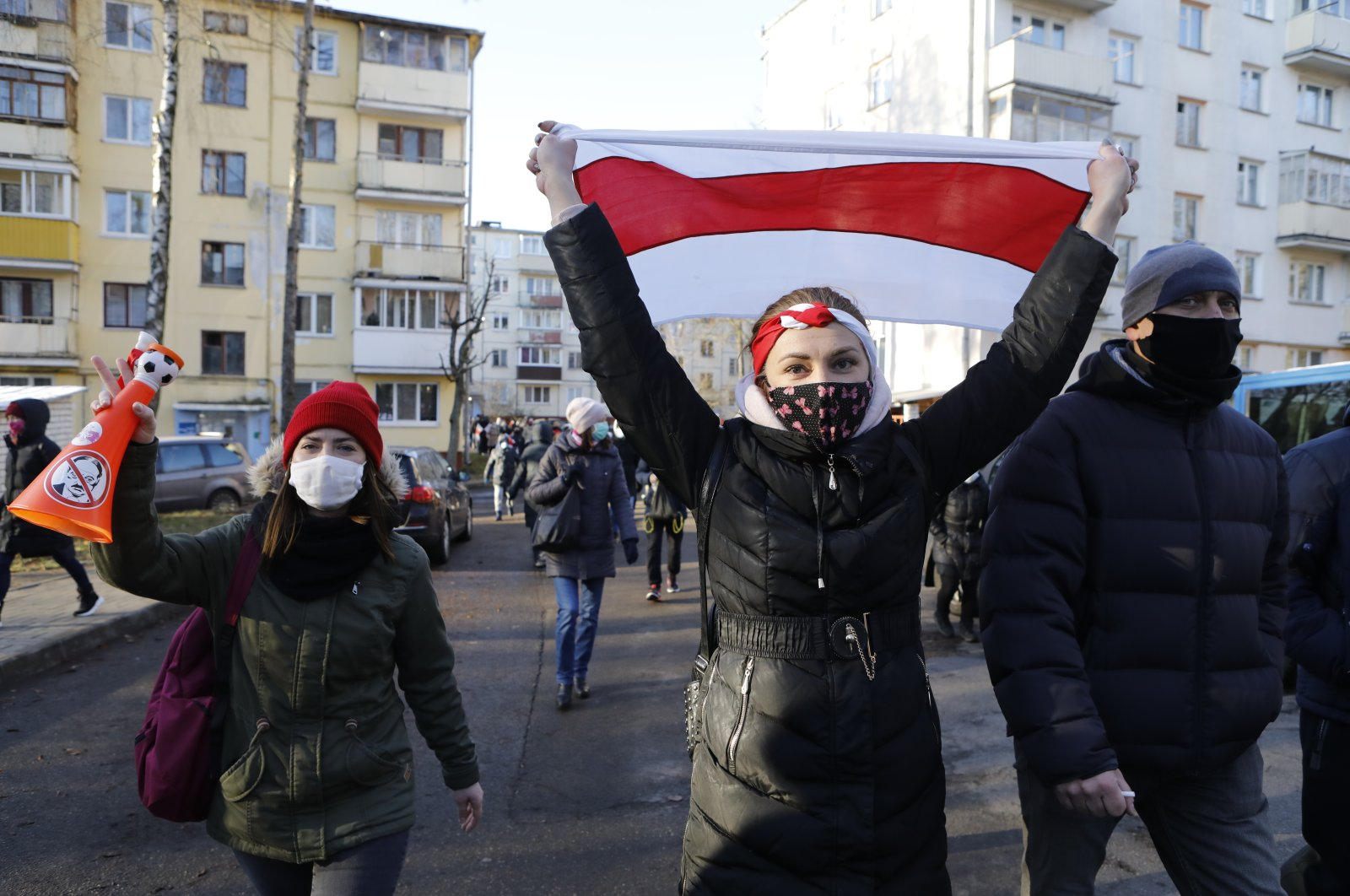 Demonstrators wearing face masks to help curb the spread of the coronavirus, at right one waves an old Belarusian national flag, during an opposition rally to protest the official presidential election results in Minsk, Belarus, Sunday, Dec. 6, 2020. (AP photo)