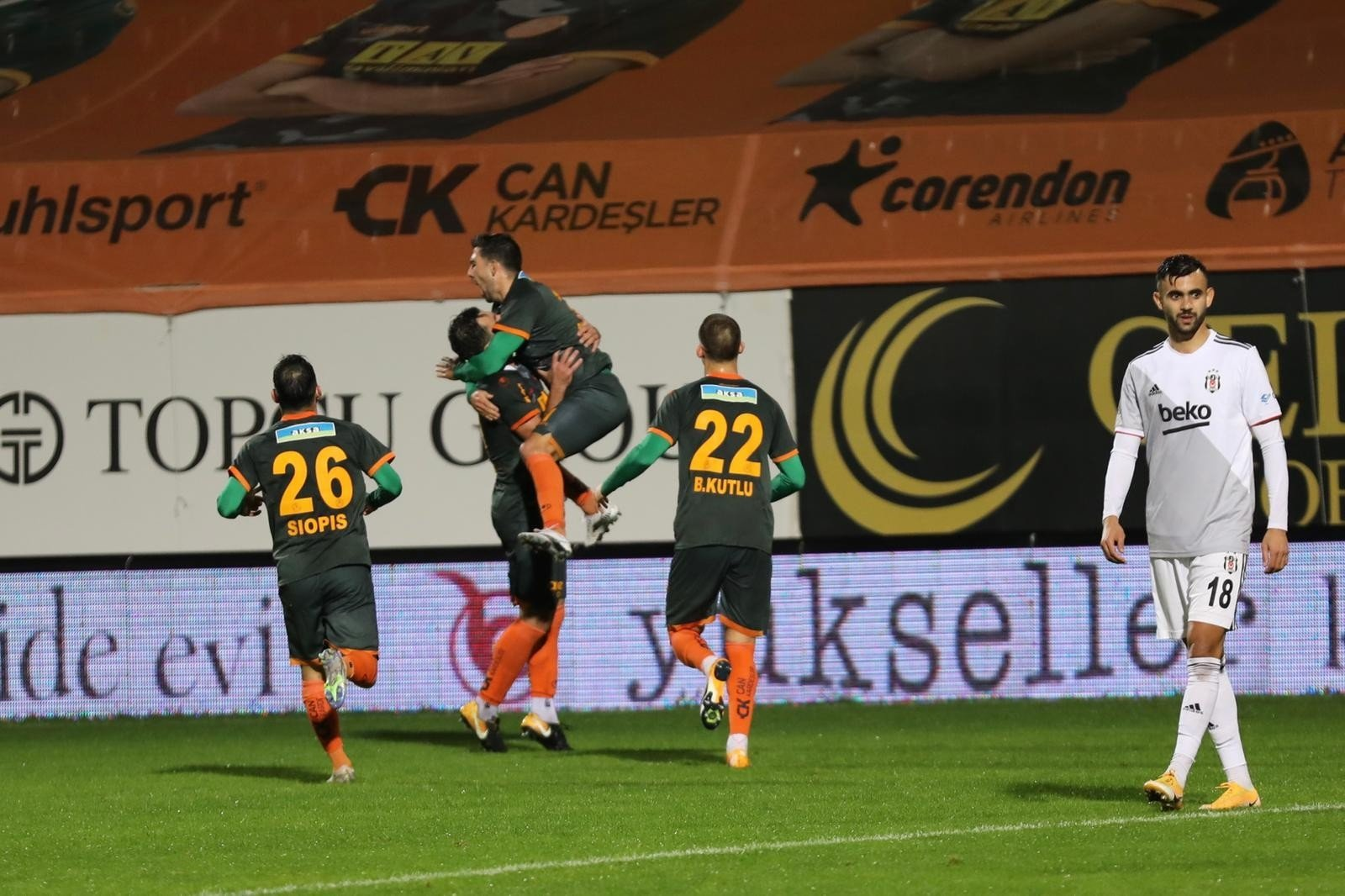 Beşiktaş's Rachid Ghezzal (R) walks across the field as Alanyaspor players celebrate winning the Süper Lig match in Antalya, Turkey, Dec. 13, 2020. (IHA Photo)