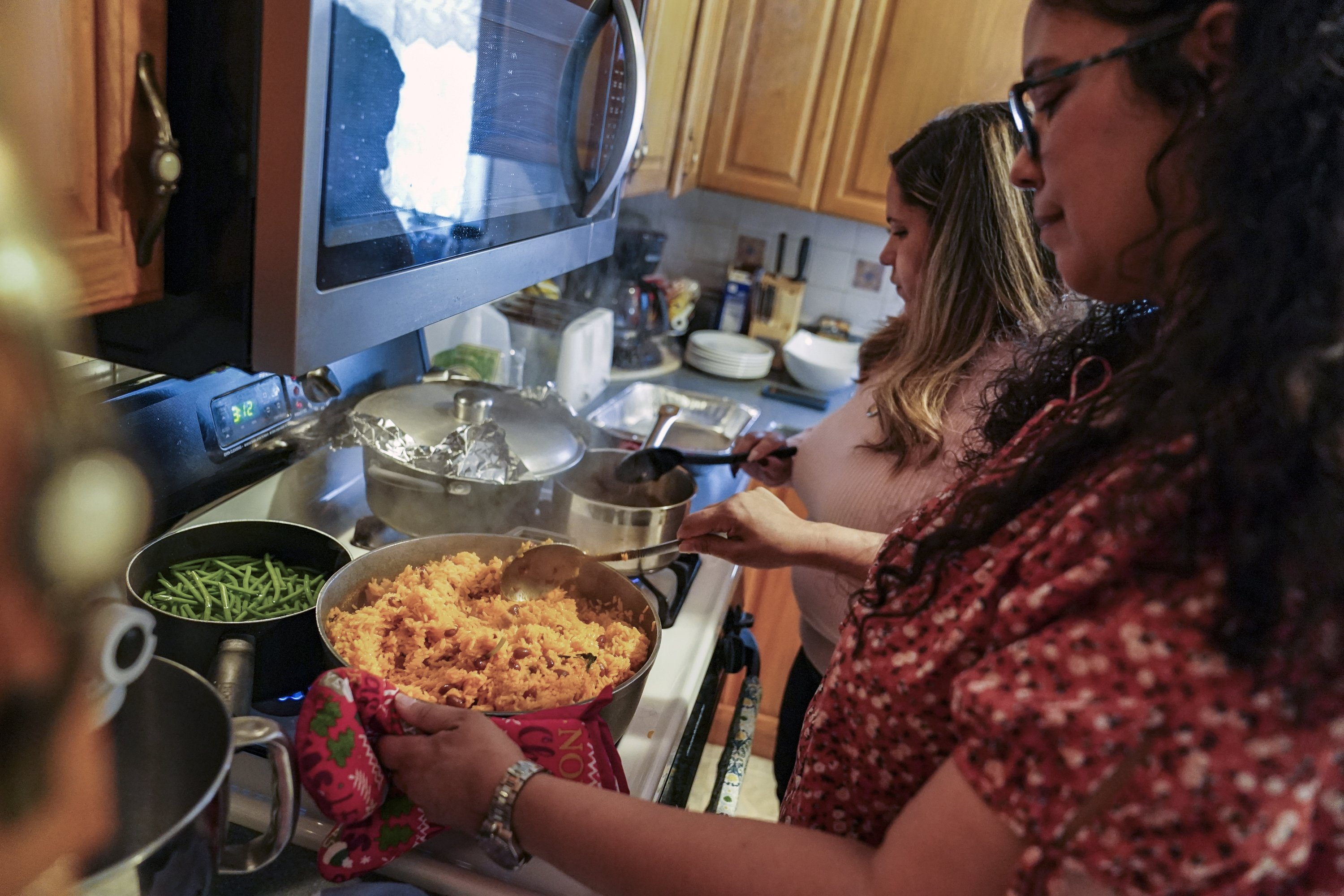 A woman cooks rice and beans by her mother's recipe as she and her sister prepare Thanksgiving dinner, Nov. 26, 2020, in Deer Park, N.Y. (AP Photo)