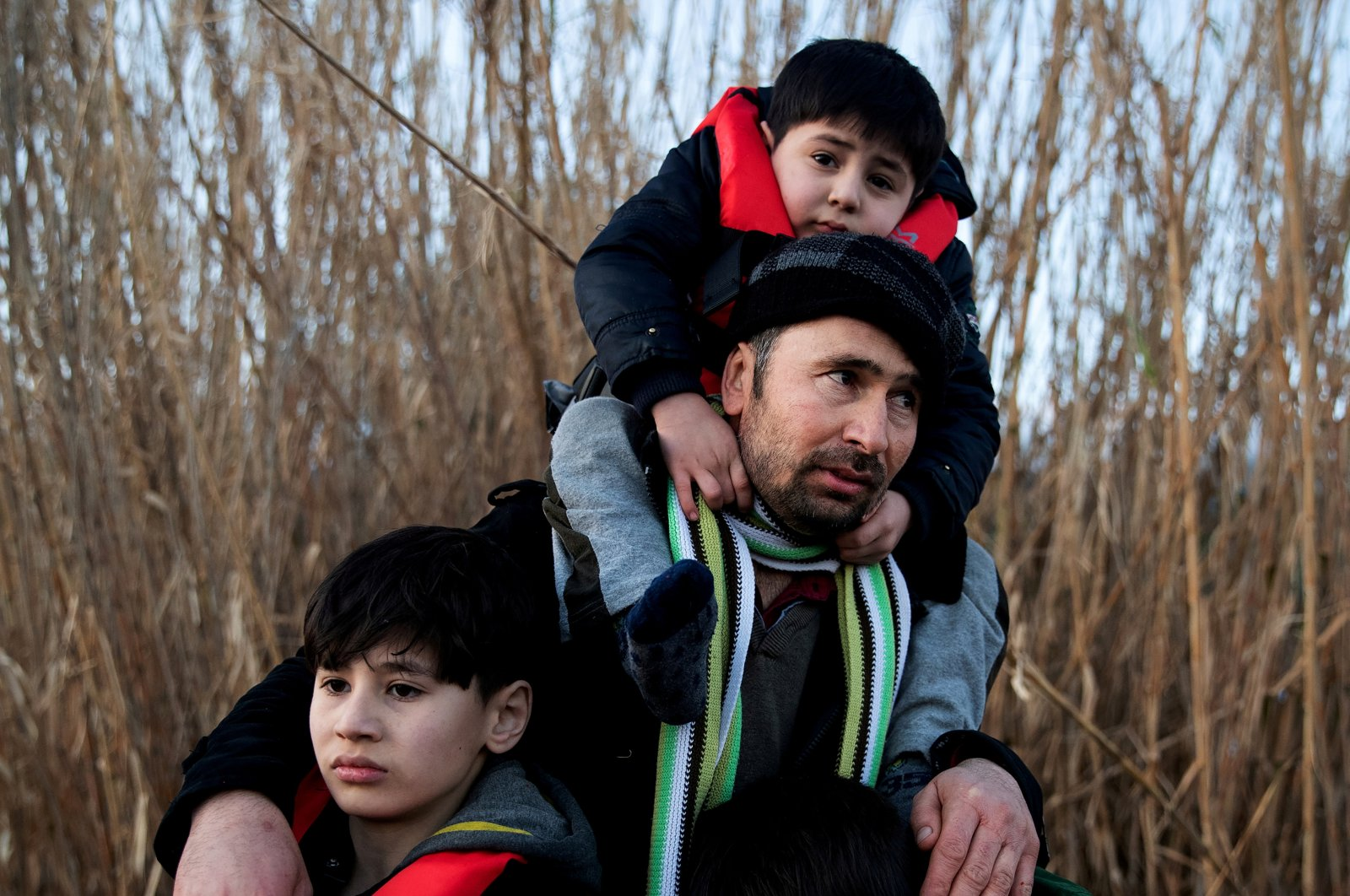 An Afghan man holds his three sons after arriving on a dinghy on a beach near the village of Skala Sikamias, after crossing part of the Aegean Sea from Turkey to the island of Lesbos, Greece, March 2, 2020. (Reuters Photo)