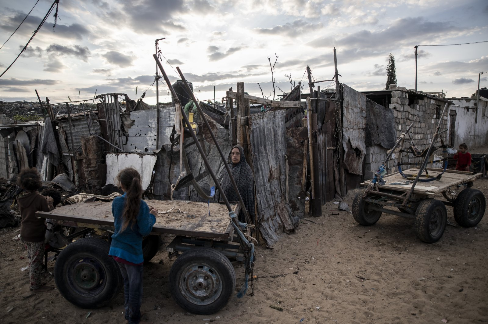 A Palestinian woman stands next to her house in a slum on the outskirts of Khan Younis Refugee Camp, in the southern Gaza Strip, Nov. 25, 2020. (AP Photo)