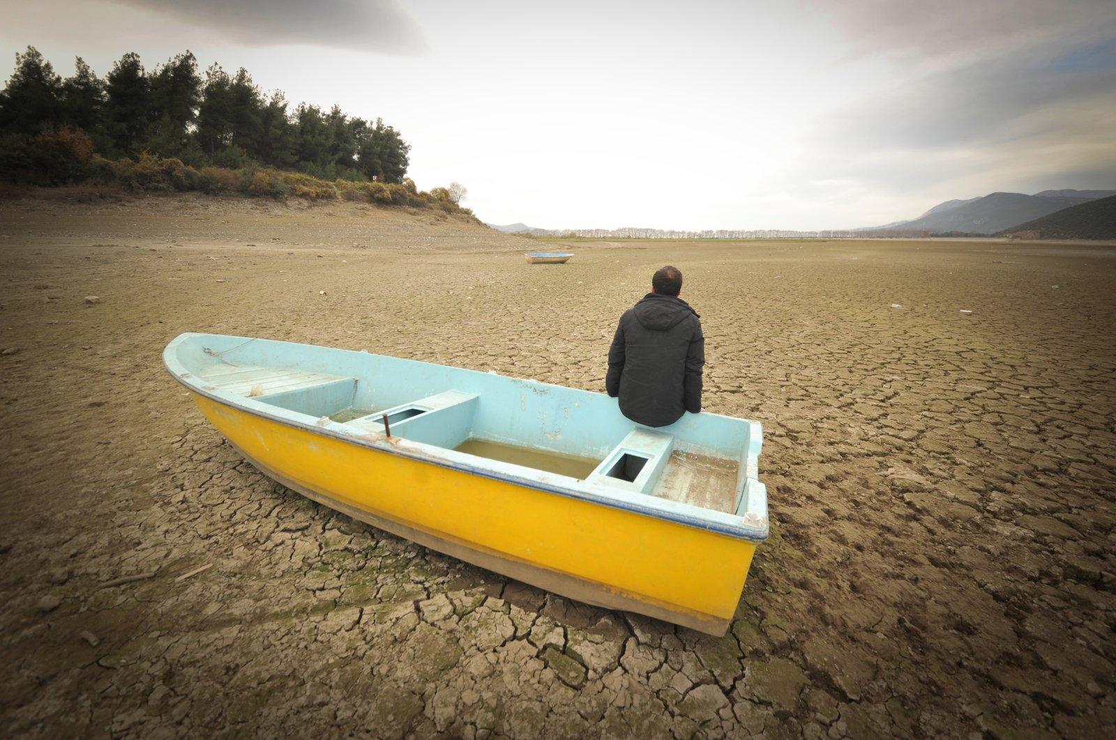 A man sits on a small boat on a dried part of Gölbaşı Dam in the Kestel district, in Bursa, northwestern Turkey, Dec. 11, 2020. (DHA PHOTO)