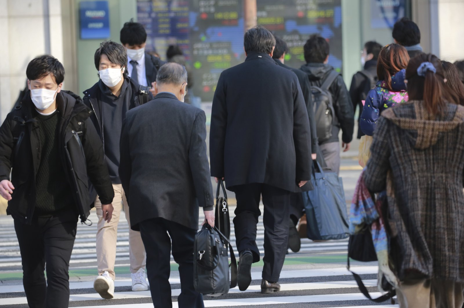 People cross an intersection on a street in Tokyo, Dec. 14, 2020. (AP Photo)