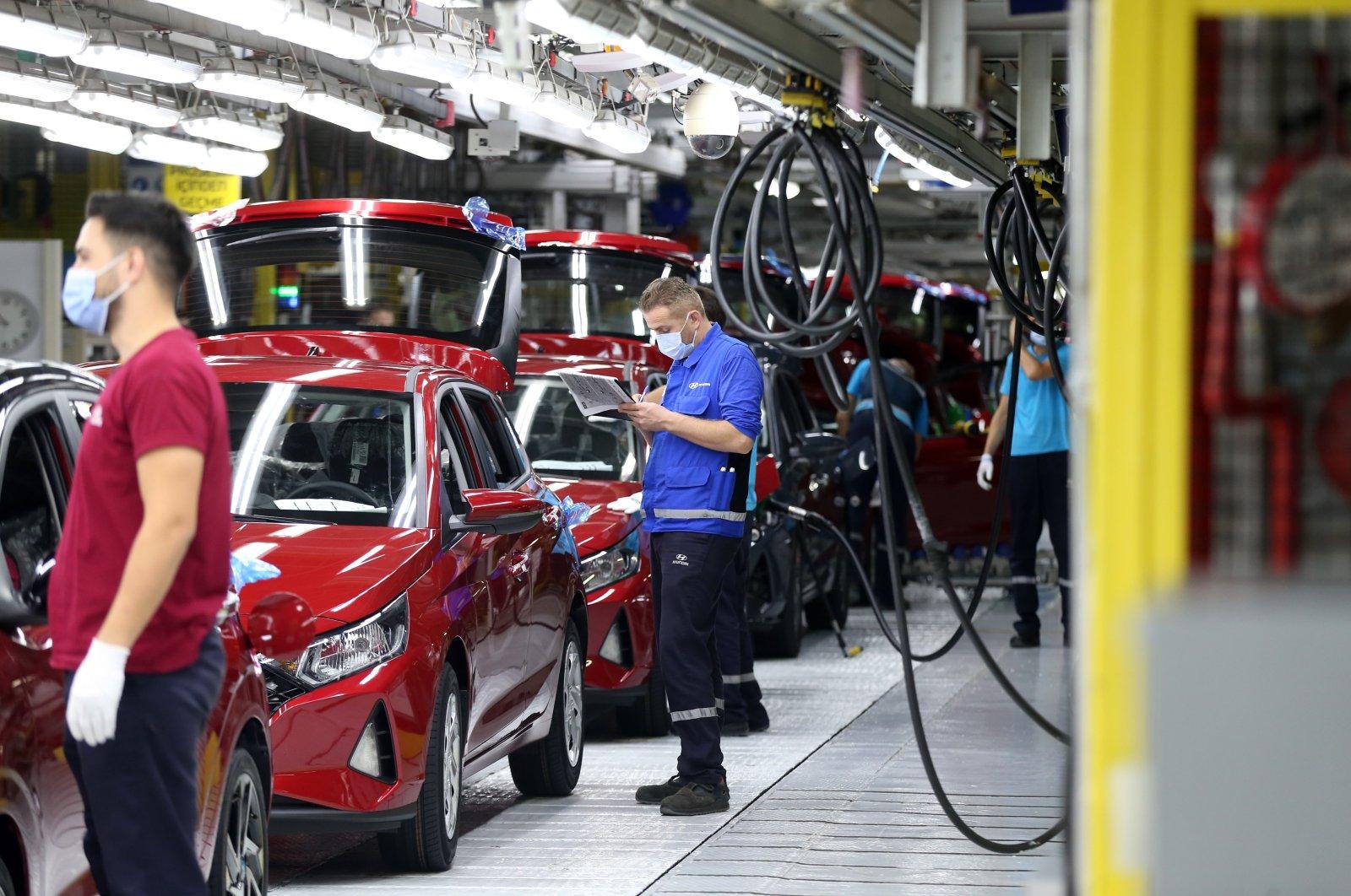 Workers are seen beside cars at Hyundai Assan's Izmit factory in northwestern Kocaeli, Turkey, Aug. 28, 2020. (AA Photo)