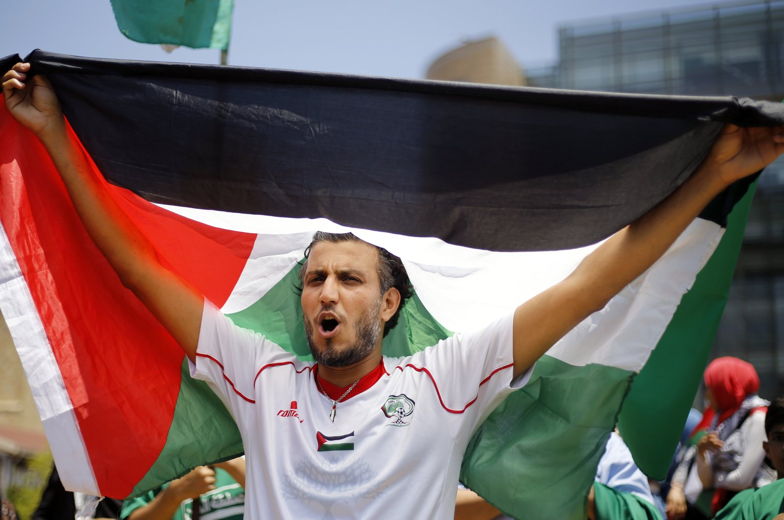 A Palestinian holds up a flag of Palestine as he chants slogans during a demonstration organized by the Hamas group in front of the United Nations headquarters in Beirut, Lebanon, June 25, 2019. (AP Photo)