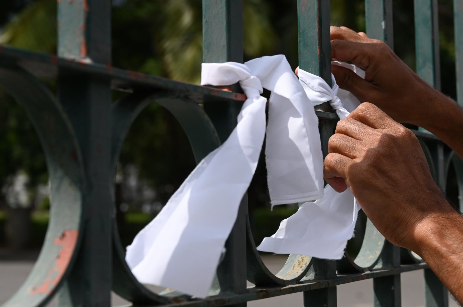 A man ties a white ribbon on a fence at a cemetery as a sign of protest against the government policy of forced cremations of Muslims who die of the coronavirus, in Colombo, Sri Lanka, Dec. 14, 2020. (AFP Photo)