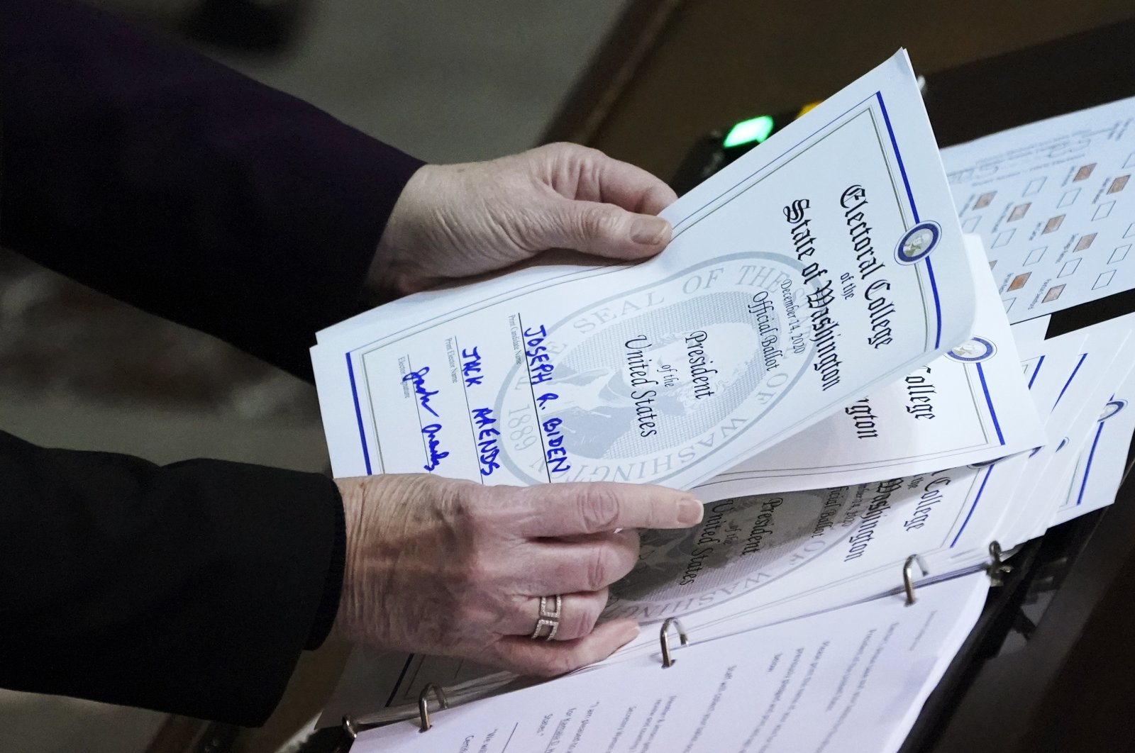Secretary of State Kim Wyman holds a ballot marked for President-elect Joe Biden that was cast by Jack Arends, a member of Washington's Electoral College, at the state Capitol in Olympia, Wash., Monday, Dec. 14, 2020. (AP Photo)