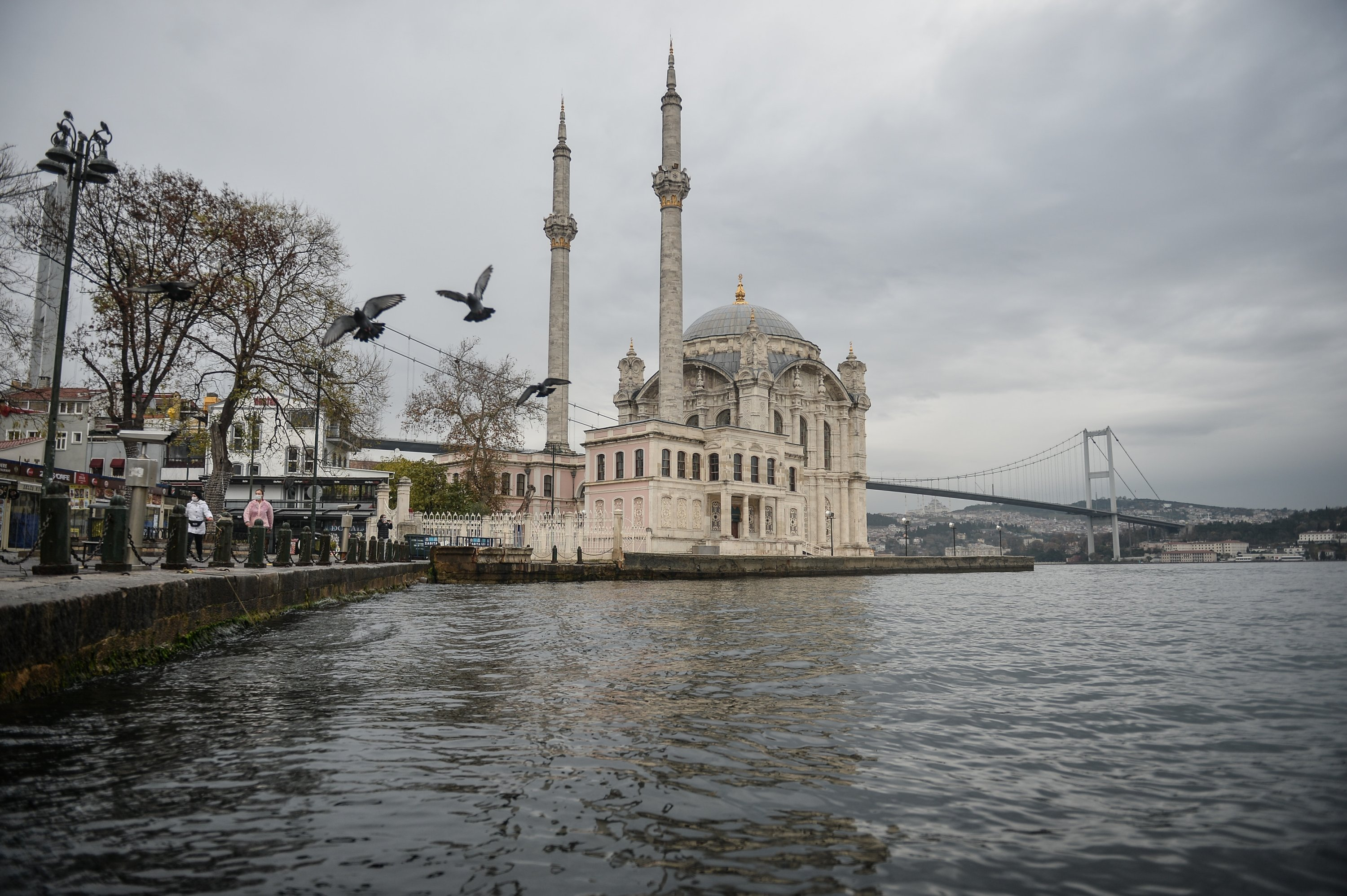 Photo shows the July 15 Democracy and Martyrs' Bridge and the Ortaköy Mosque as two pigeons fly over the waters of the Bosporus in Istanbul, December 12, 2020. (DHA Photo)
