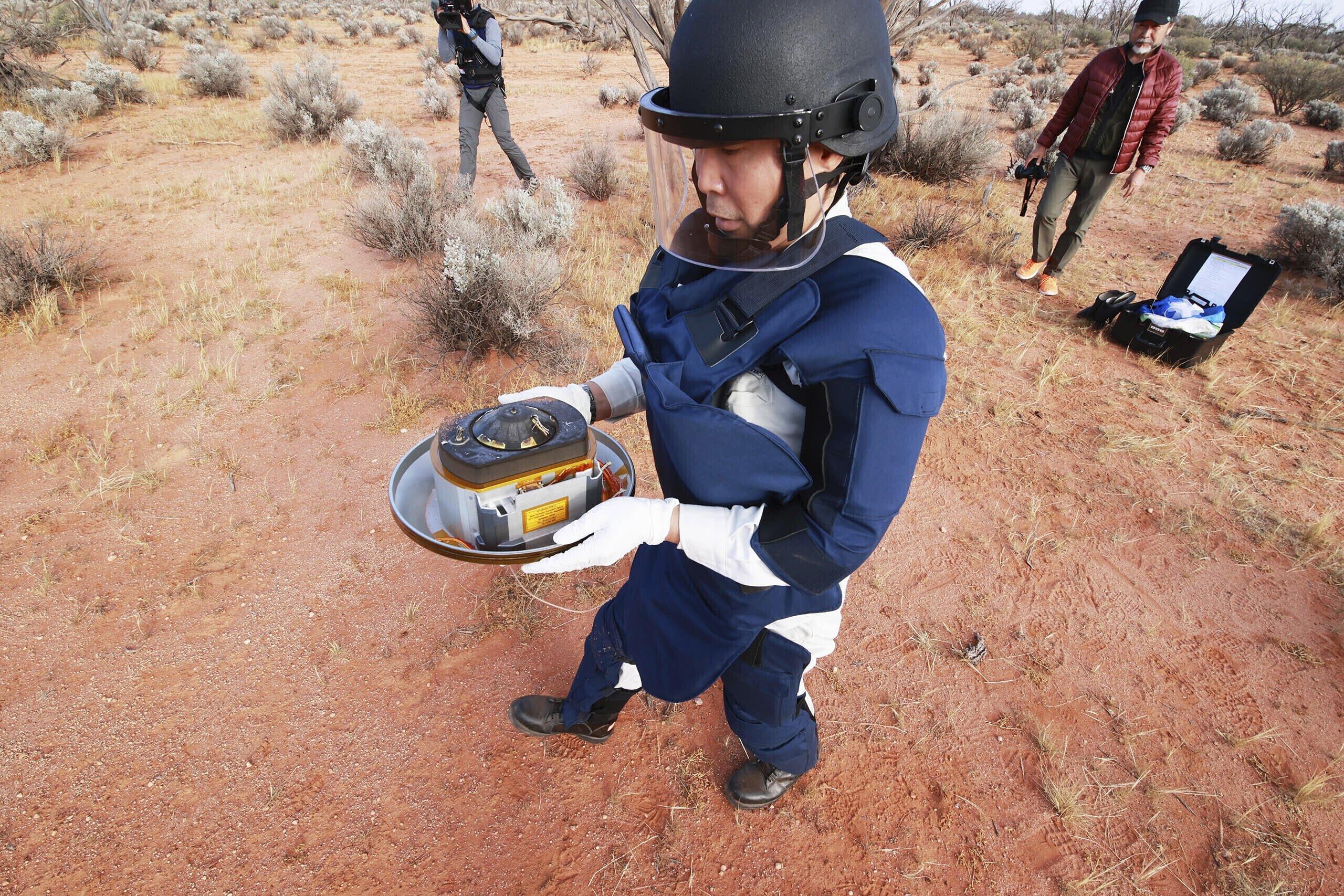 A member of the Japan Aerospace Exploration Agency (JAXA) retrieves a capsule dropped by Hayabusa2 in Woomera, southern Australia, Dec. 6, 2020. (Photo provided by JAXA via AP)