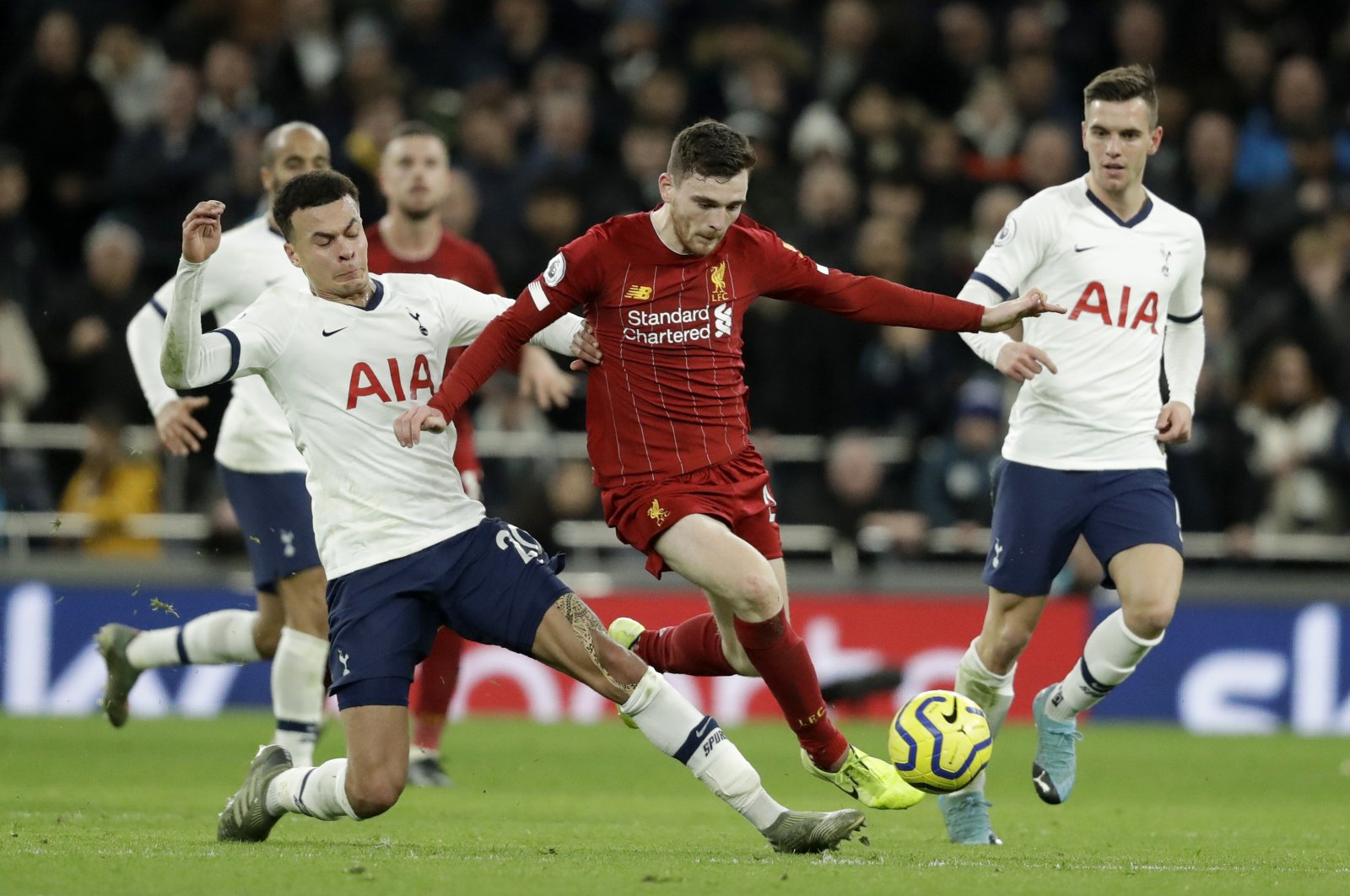 Tottenham's Dele Alli (L) fights for the ball with Liverpool's Andrew Robertson (C) during a Premier League match at the Tottenham Hotspur Stadium in London, England, Jan. 11, 2020. (AP Photo)