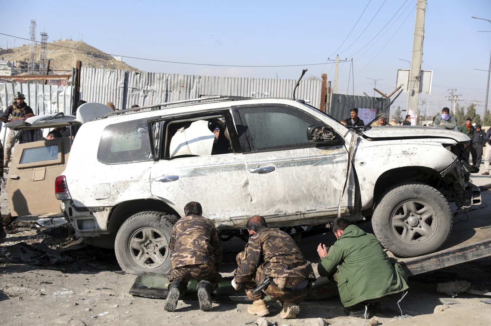 Afghan security personnel inspect the site of a bomb attack in Kabul, Afghanistan, Dec. 15, 2020. (AP Photo)