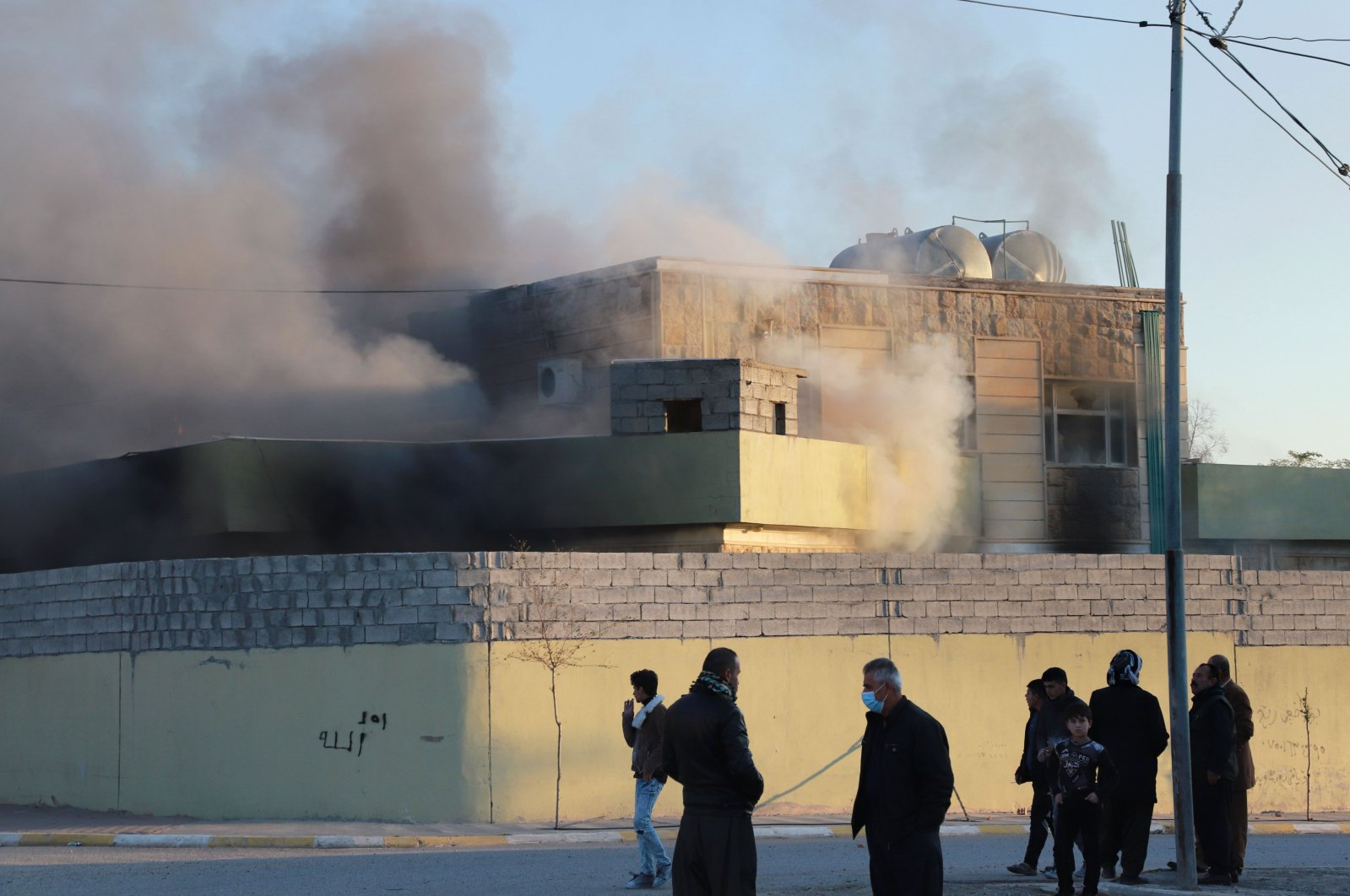 People stand outside a local police station set on fire by protesters in the town of Takia, about 60 kilometers southwest of the city of Sulaimaniyah, on Dec. 8, 2020. (AFP Photo)