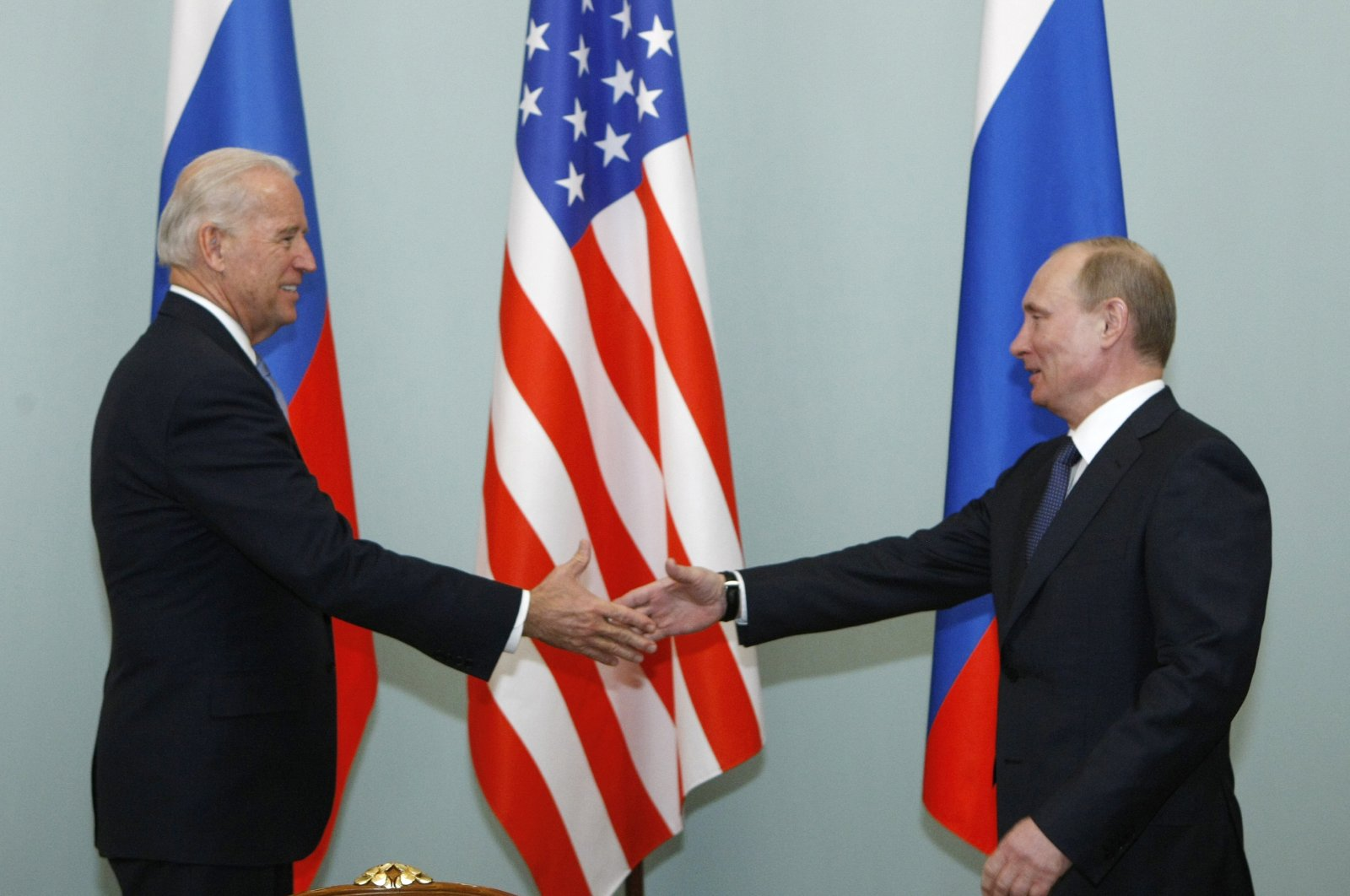In this file photo, then-U.S. Vice President Joe Biden (L) shakes hands with Russian Prime Minister Vladimir Putin in Moscow, Russia, March 10, 2011. (AP Photo)