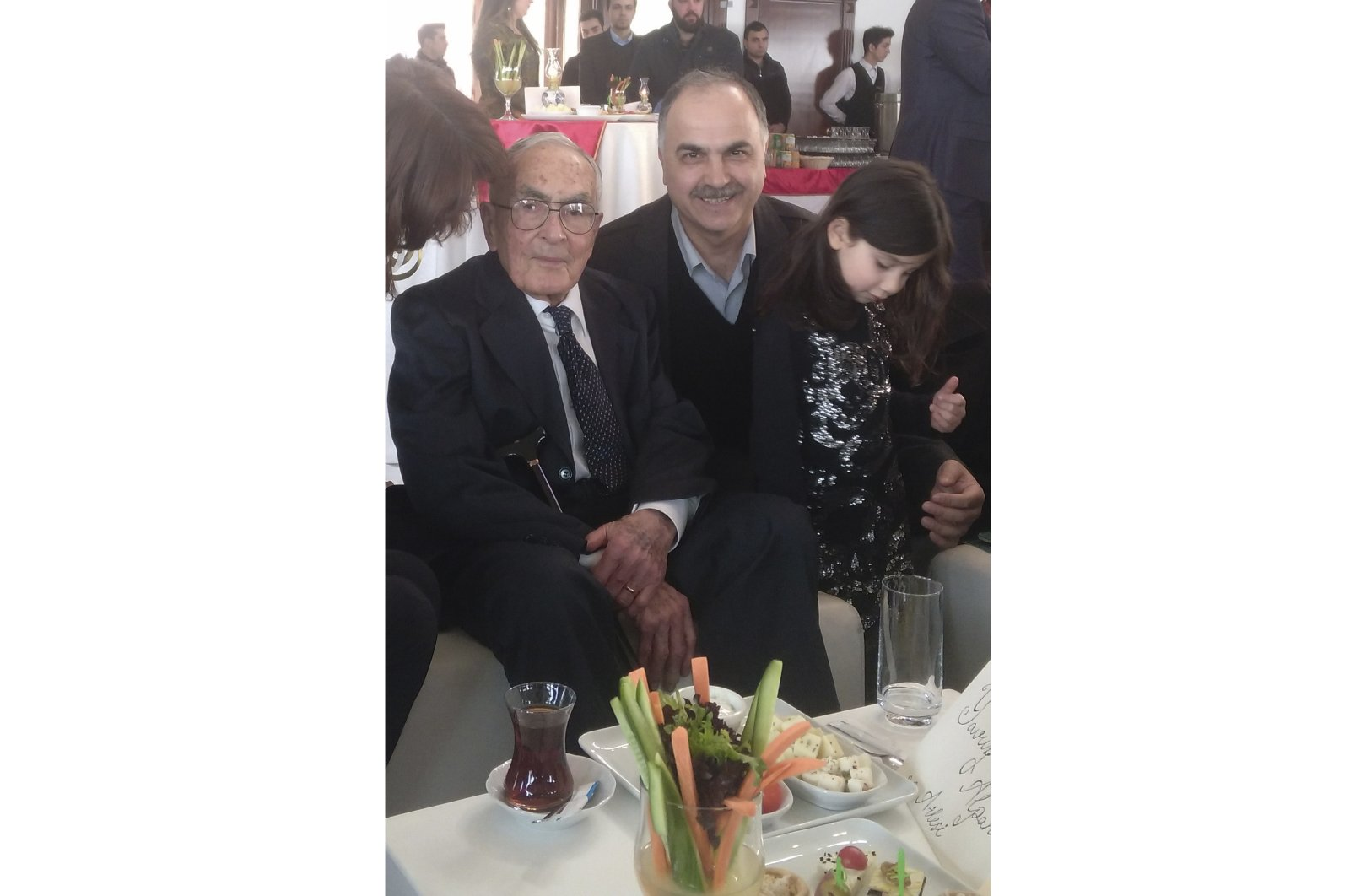 """Sultanzade Yavuz Alpan (L) poses for the camera with his granddaughter Aya and historian Ibrahim Pazan at the gala of the documentary """"Bilun: The Last Witness of Exile"""" in Istanbul on Feb. 28, 2017. (IHA Photo)"""