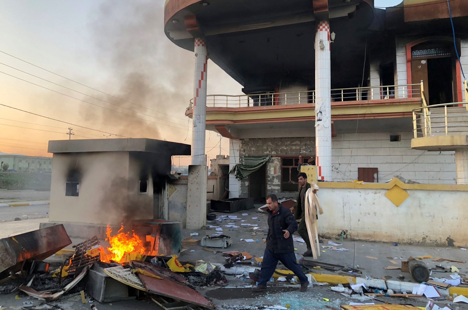 Men are seen outside the headquarters of the Kurdistan Democratic Party (KDP) after it was set on fire during anti-government protests on the outskirt of Sulaimaniyah, Iraq, Dec., 8, 2020. (REUTERS Photo)