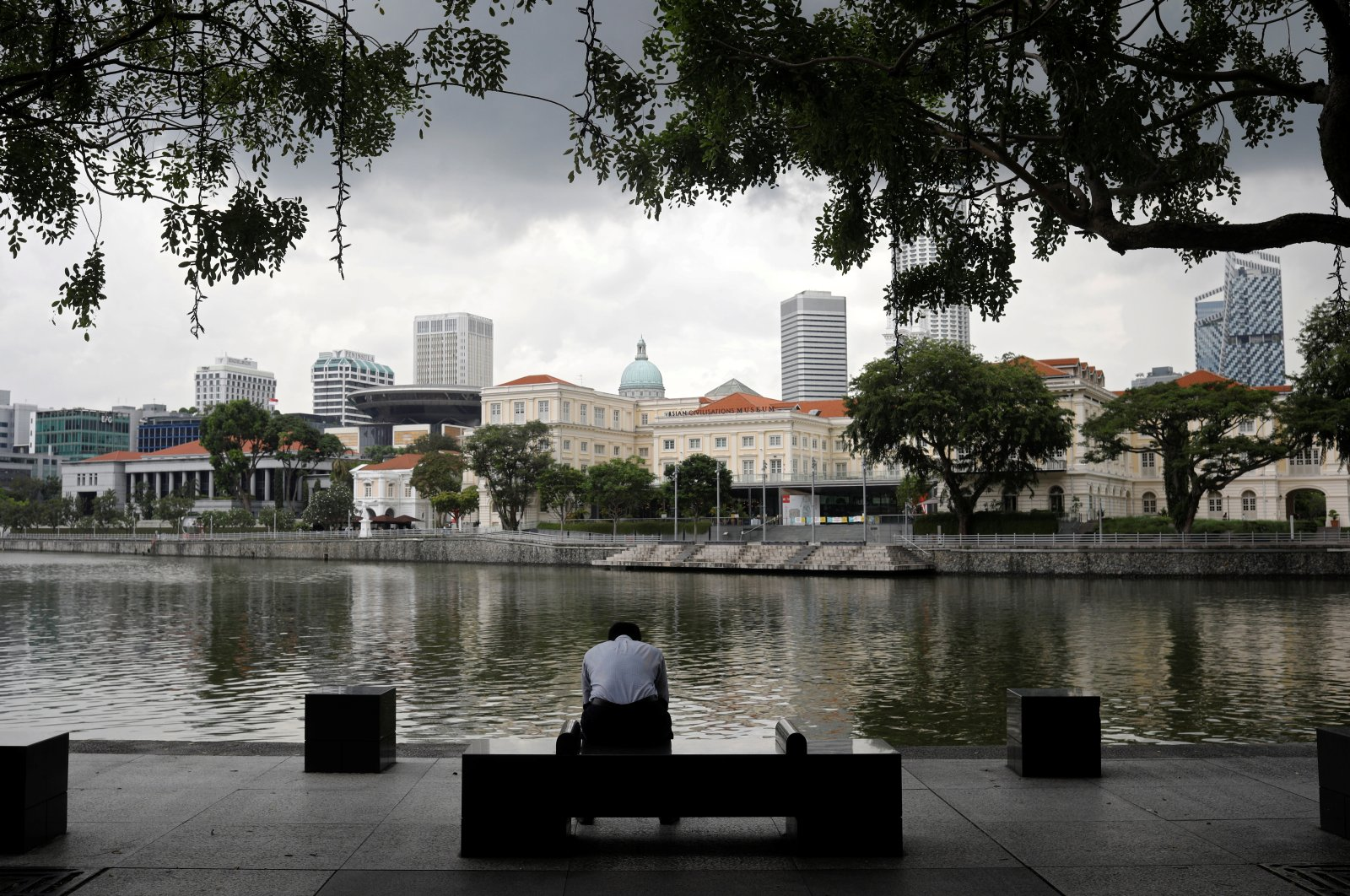 An office worker sits by the river side during lunch hour at the central business district in Singapore December 14, 2020. (Reuters Photo)