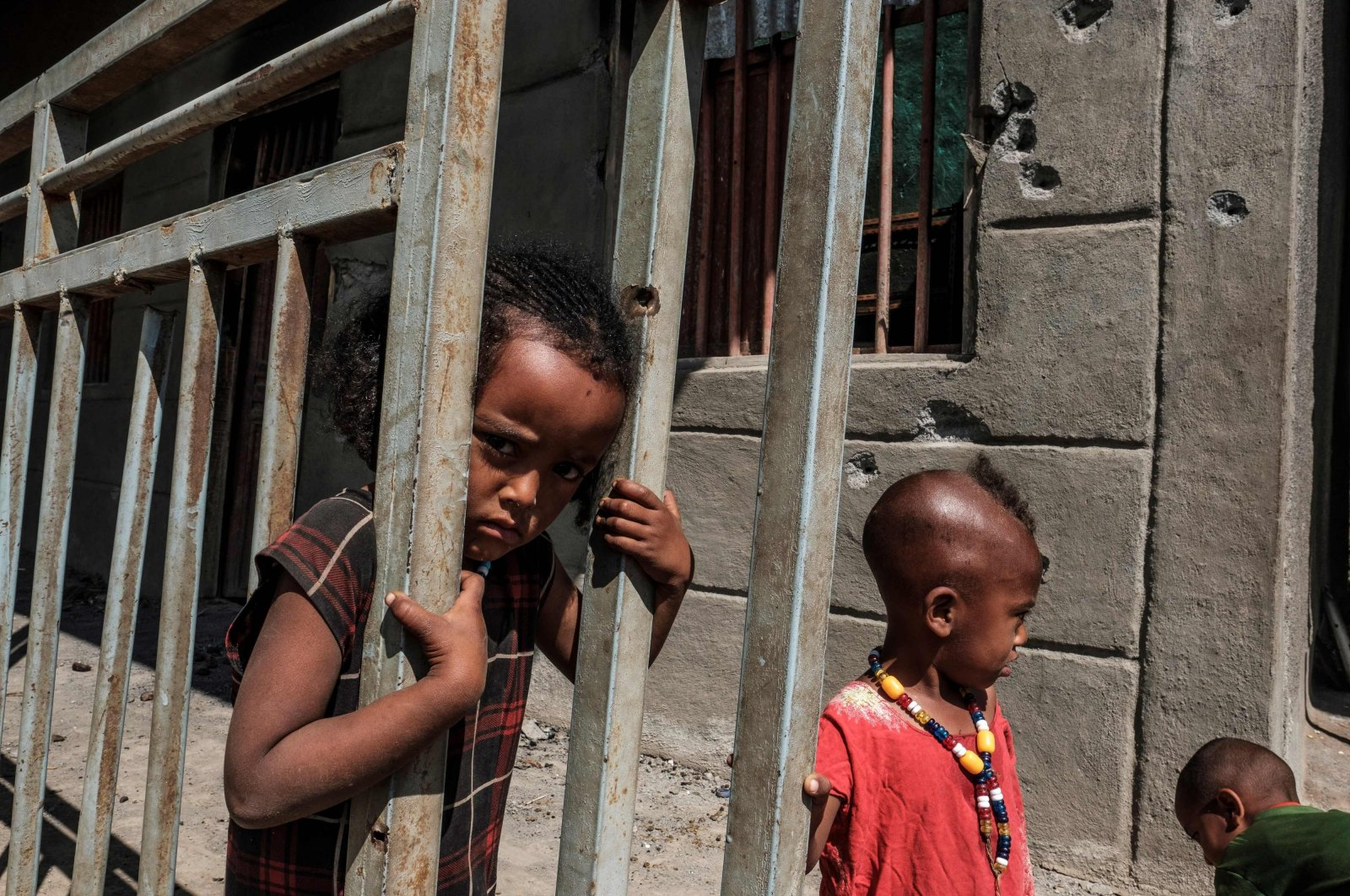 Children play in front of a store damaged by bullets in the village of Bisober, in Ethiopia's Tigray region on Dec. 9, 2020. (AFP Photo)