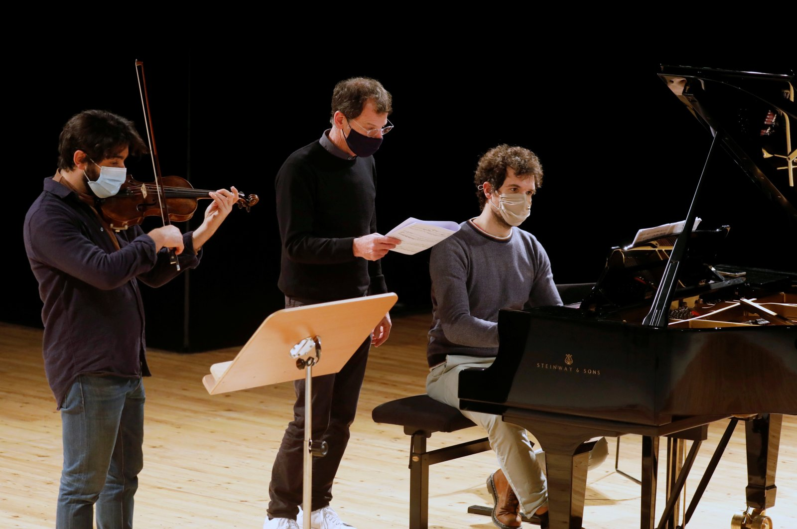 Violinist Yoan Brakha, director Simon Valastro and pianist Felix Ramos, members of the Opera de Paris Academy, rehearse in masks at the Bastille Opera in Paris, France, Dec. 11, 2020. (Reuters Photo)