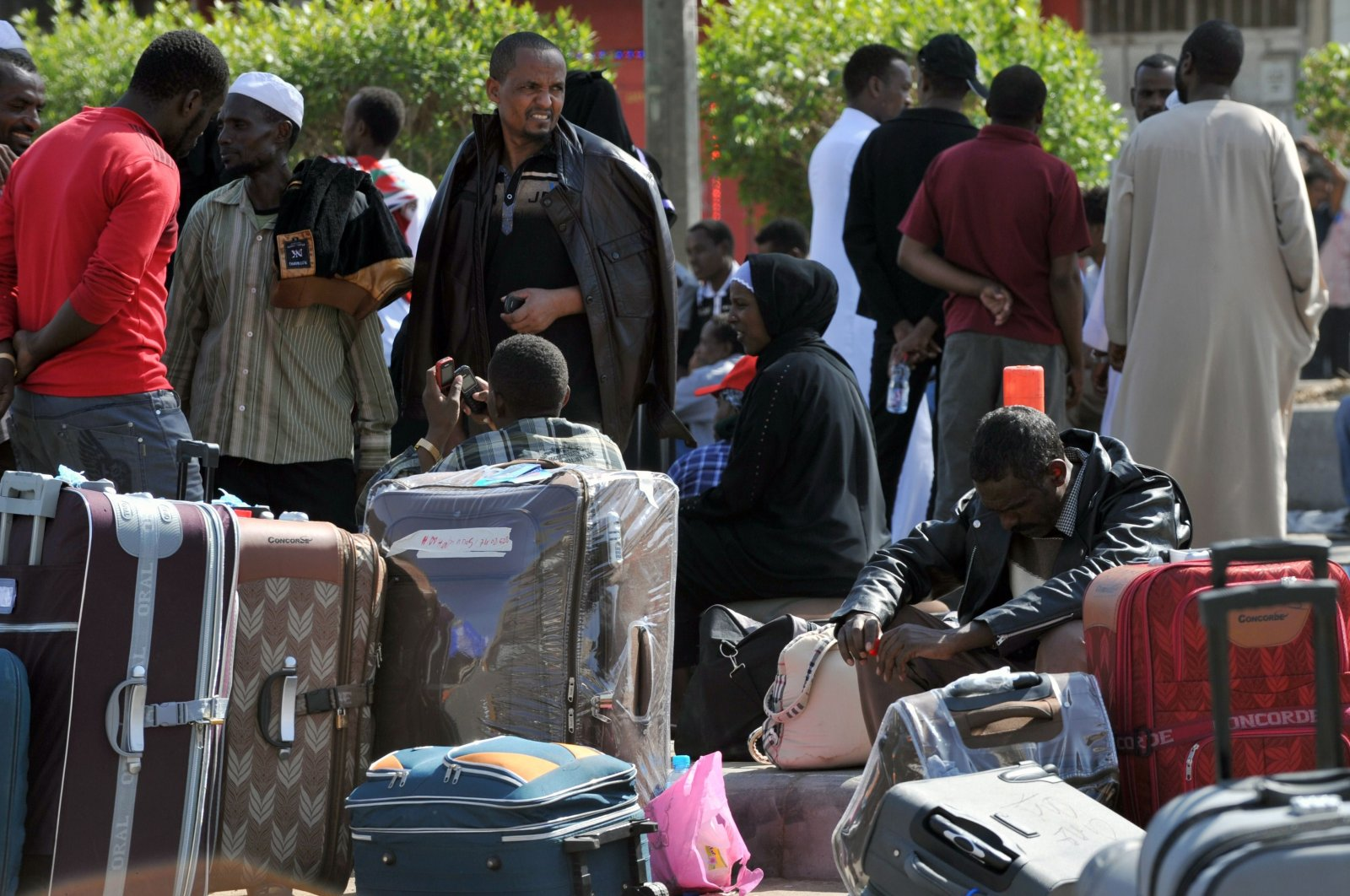 Foreign workers wait with their belongings before boarding police buses transferring them to an assembly center prior to their deportation in Riyadh, Saudi Arabia, Nov. 12, 2013. (AFP Photo)