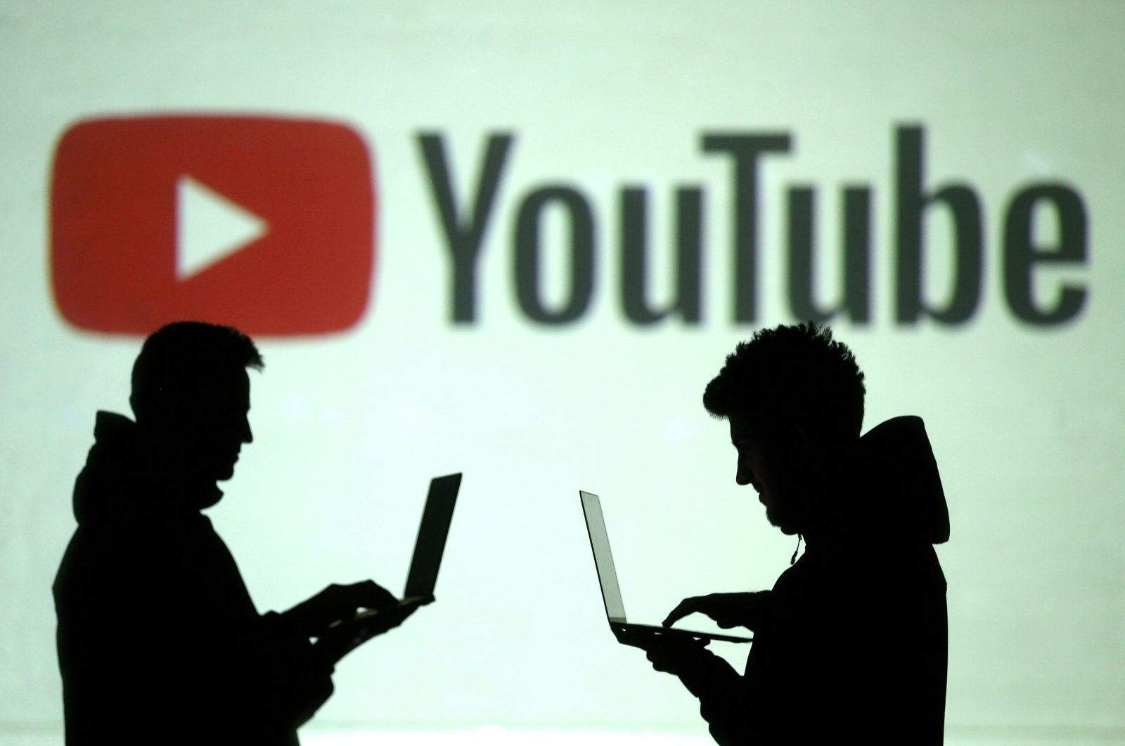 Silhouettes of mobile device users are seen next to a screen projection of the YouTube logo in this picture illustration taken March 28, 2018.  (Reuters Photo)