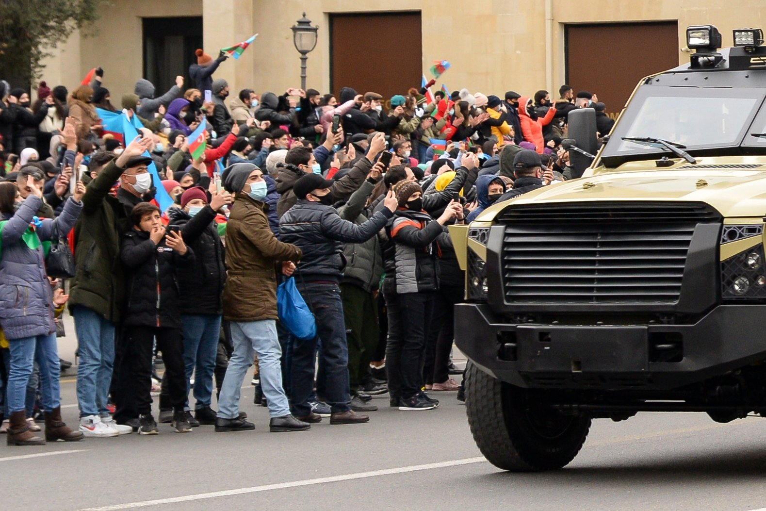 People greet Azerbaijani servicepeople riding in military vehicles during a parade marking Azerbaijan's victory against Armenia in their conflict for control over the Nagorno-Karabakh region, in Baku on Dec. 10, 2020. (AFP)