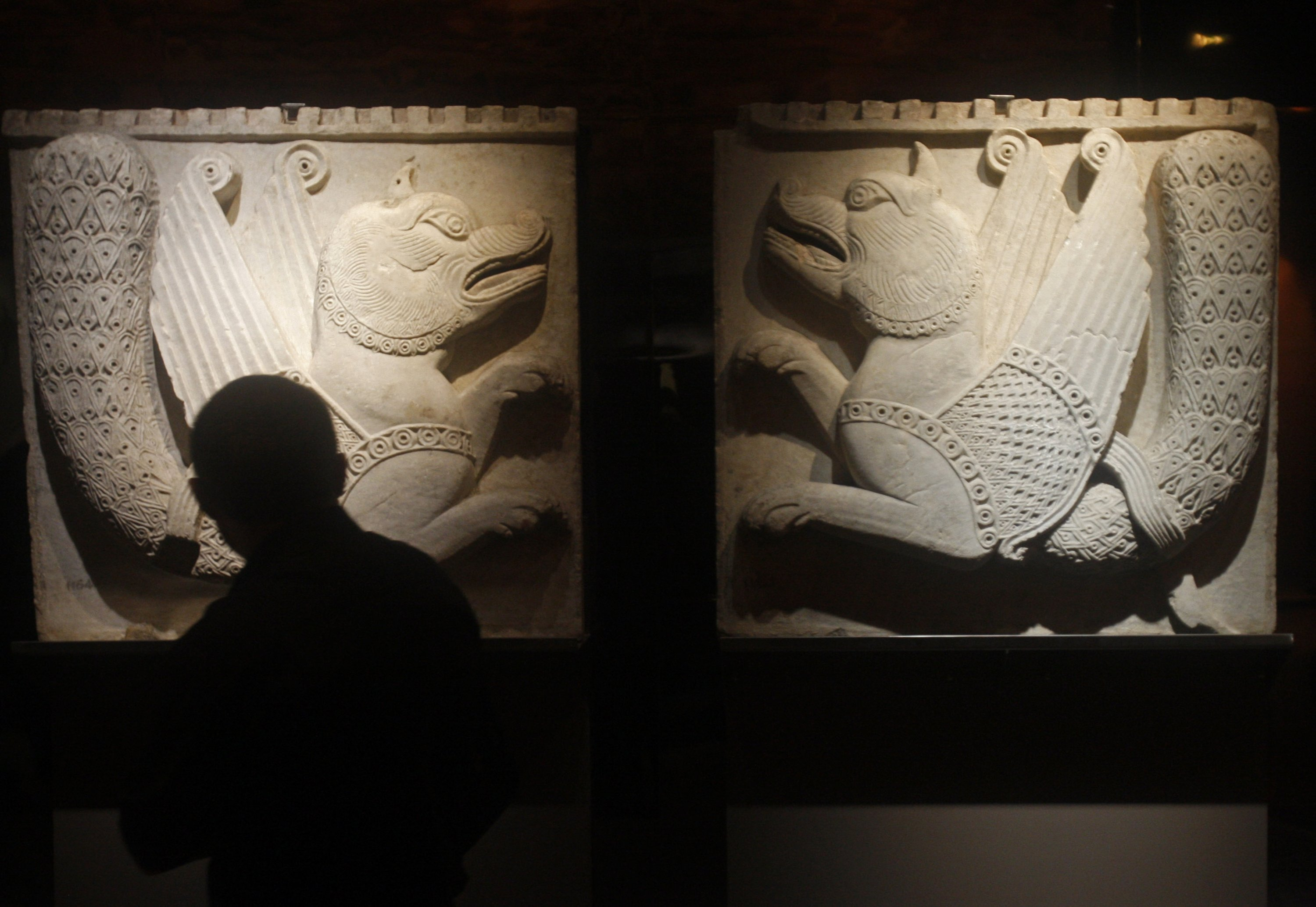 A visitor looks on two Simurgh relief, a mythical medieval creature, at the exhibition from Byzantium to Istanbul at the Grand Palais in Paris, on Oct. 21, 2009. (AP PHOTO)