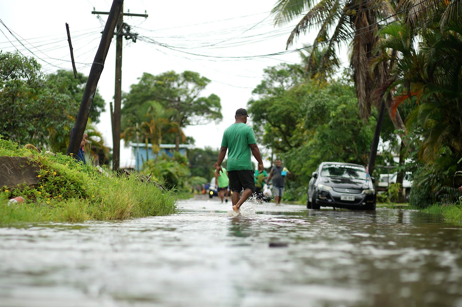 Residents wade through flooded streets in Suva, Fiji, Dec. 16, 2020, ahead of Cyclone Yasa. (AFP Photo)