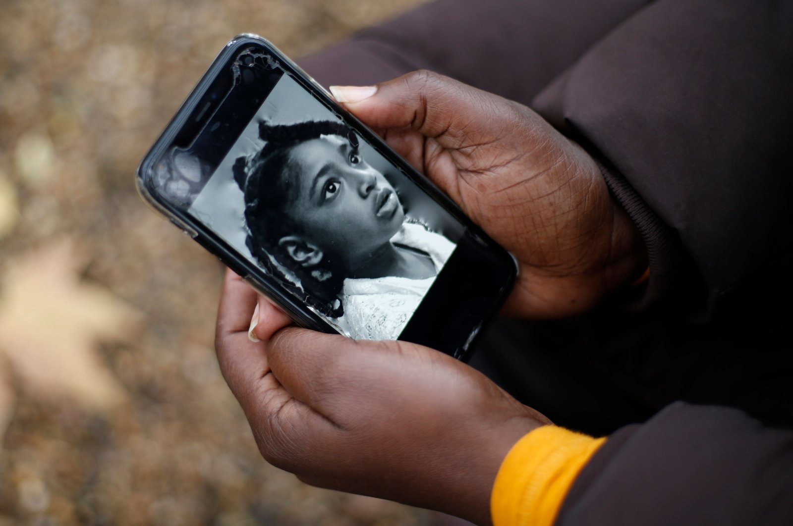 Rosamund Adoo-Kissi-Debrah holds her mobile phone displaying a photograph of her daughter Ella Adoo-Kissi-Debrah who died in February 2013 from a severe asthma attack, ahead of the opening of a coroner's inquest into the girl's death in London, Britain, Nov. 30, 2020. (AFP Photo)