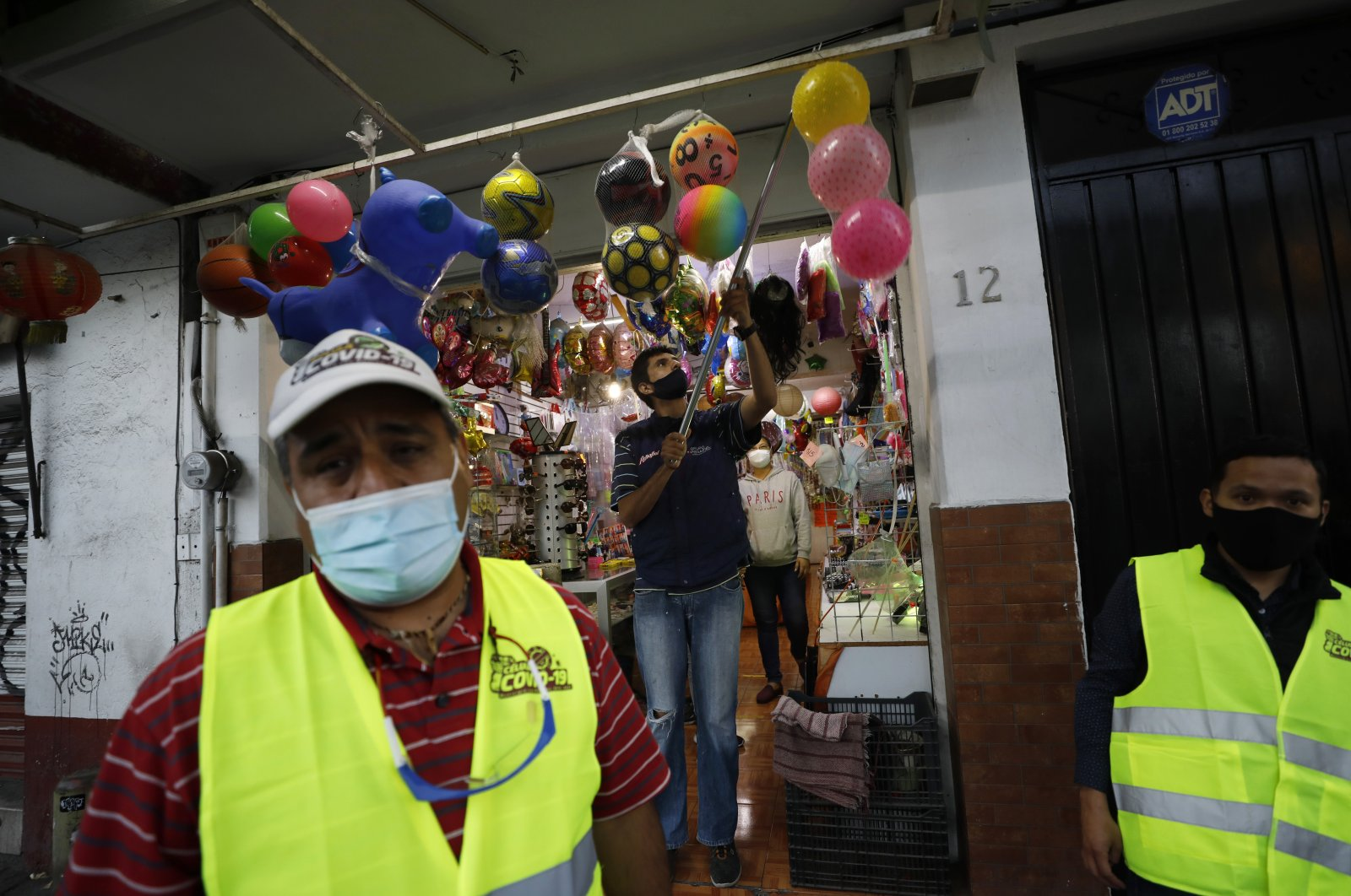 Workers begin to close shop after a visit by municipal public safety officers urging them to comply with a new state mandate saying nonessential businesses need to close at 5 p.m., to help slow the spread of COVID-19, in Ecatepec, Mexico State, on the outskirts of Mexico City, Dec. 14, 2020. (AP Photo)
