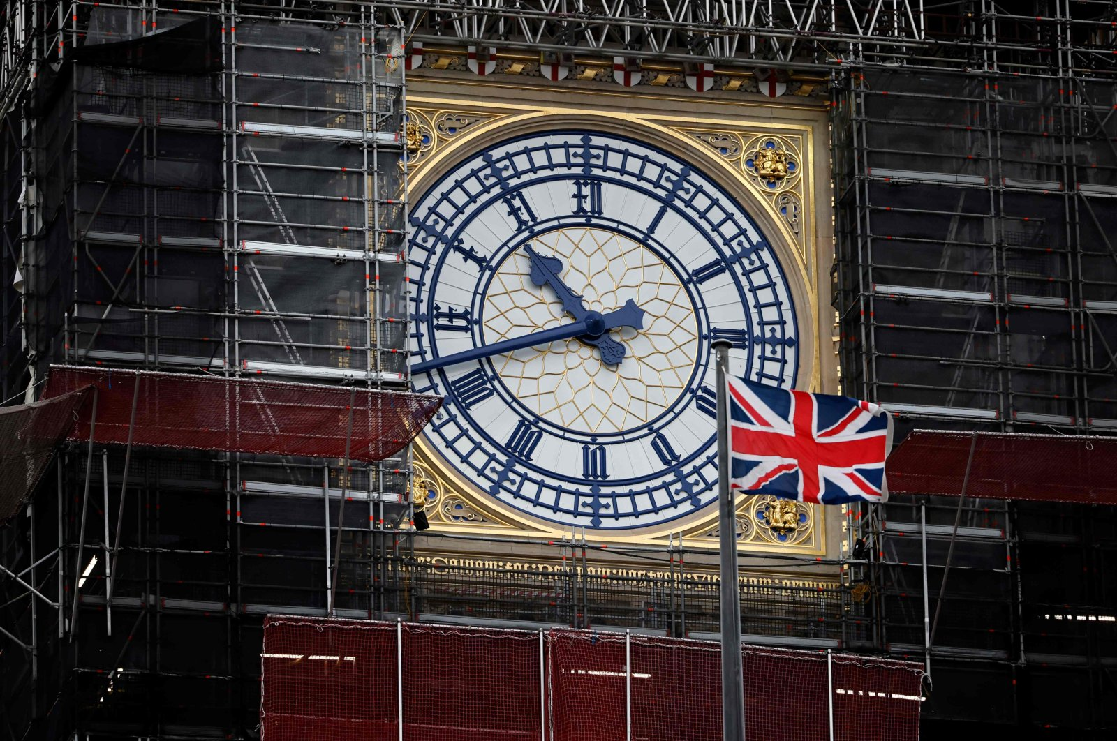 A U.K. flag flutters in the breeze in front of the clock face of the Elizabeth Tower, known after the bell Big Ben, in central London, Britain, Dec. 13, 2020. (AFP Photo)