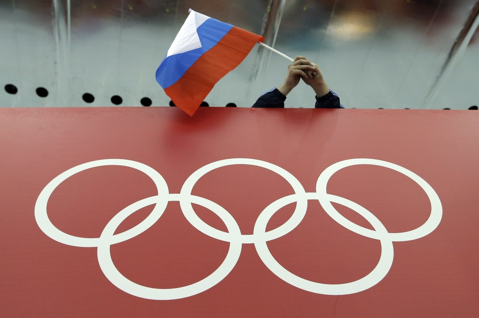 A Russian flag is held above the Olympic Rings at Adler Arena Skating Center during the Winter Olympics in Sochi, Russia on Feb. 18, 2014. (AP Photo)