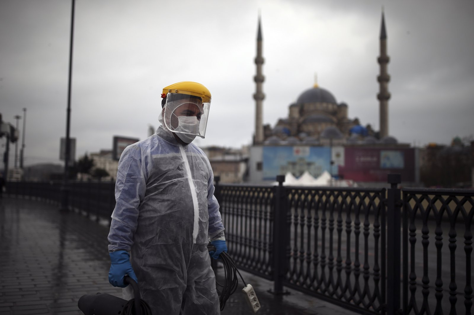 A municipality worker wearing a protective suit to help curb the spread of the coronavirus, walks to spray disinfectant on Galata Bridge over the Golden Horn in Istanbul, Turkey, Dec. 15, 2020. (AP Photo)