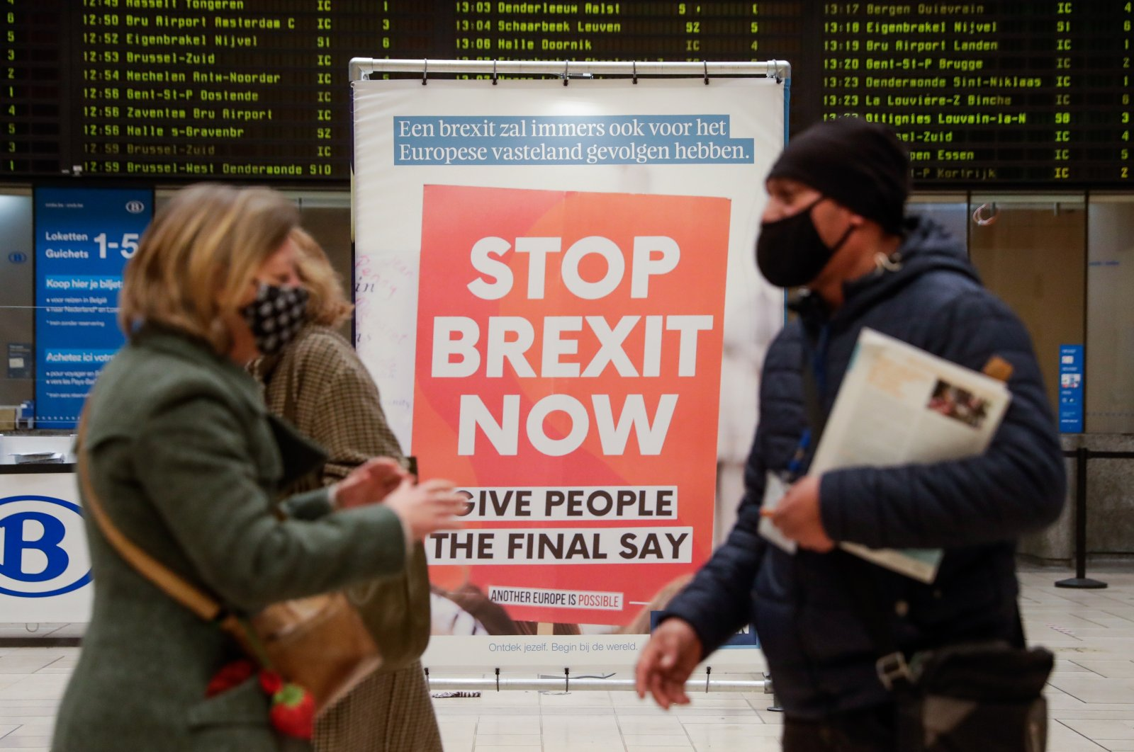 Commuters pass an anti-Brexit billboard made by the KU Leuven University at the Central Station in Brussels, Belgium on Dec. 17, 2020. (EPA Photo)