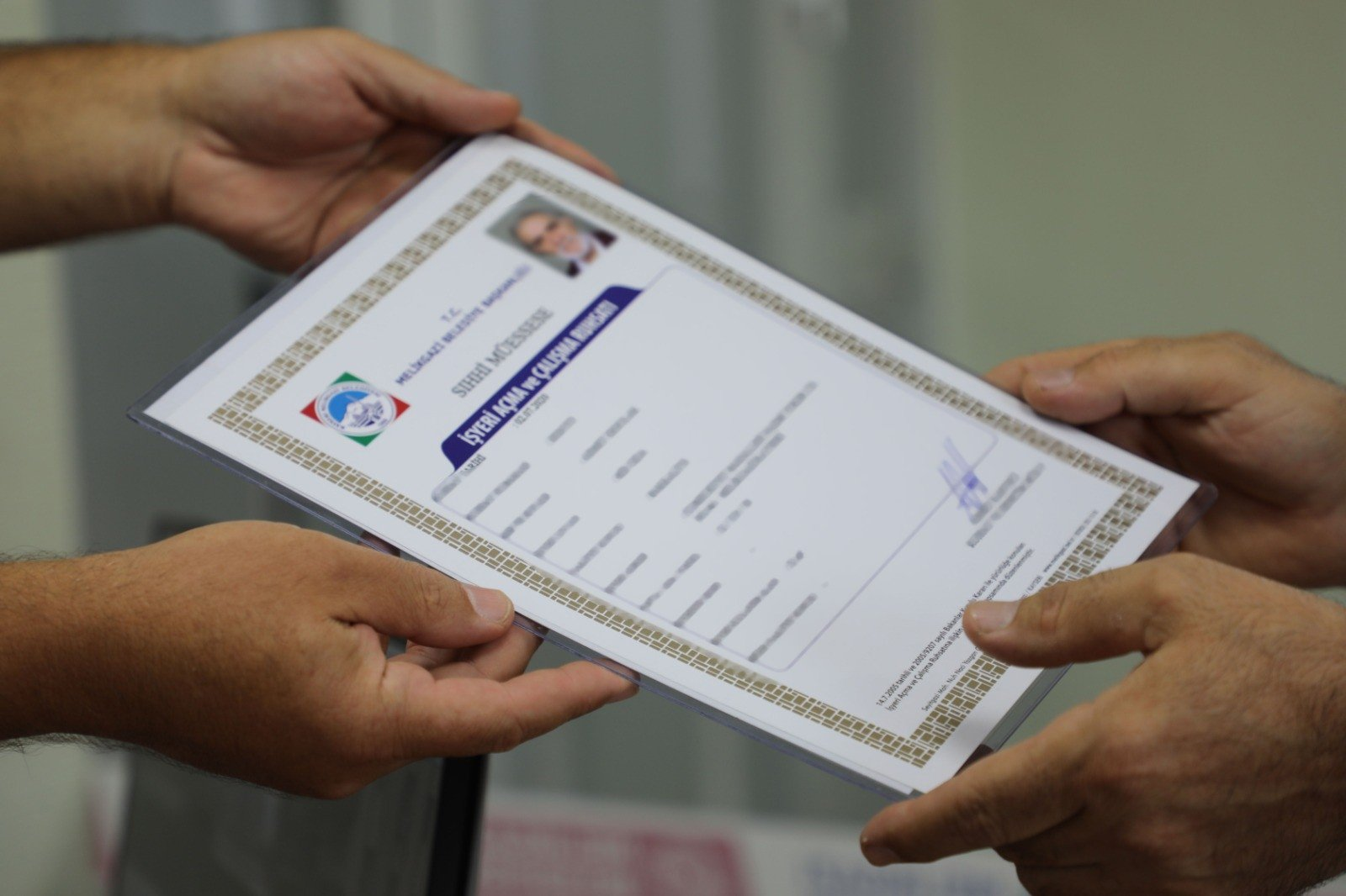 A man hands another person a license to open a workplace in Melikgazi, Konya province, central Turkey, Oct. 12, 2020. (IHA Photo)