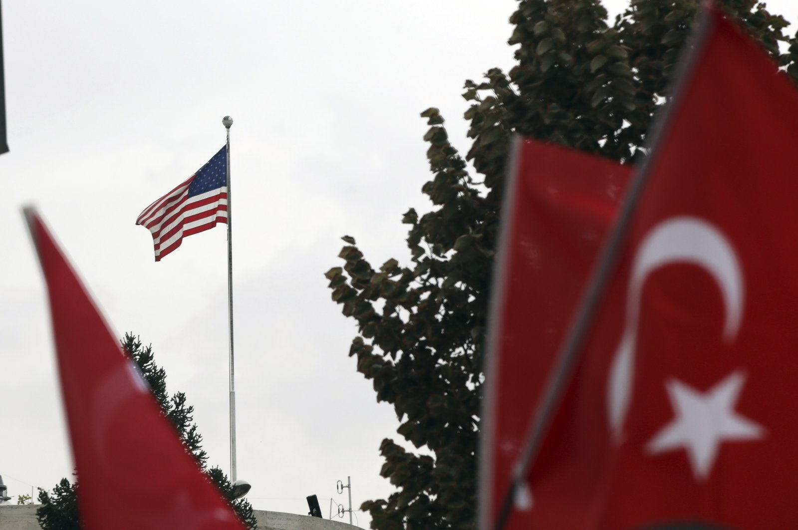 People hold national flags during a protest near the U.S. embassy, seen with a U.S. flag flying above it, in the capital Ankara, Turkey, Oct. 8, 2019. (AP Photo)