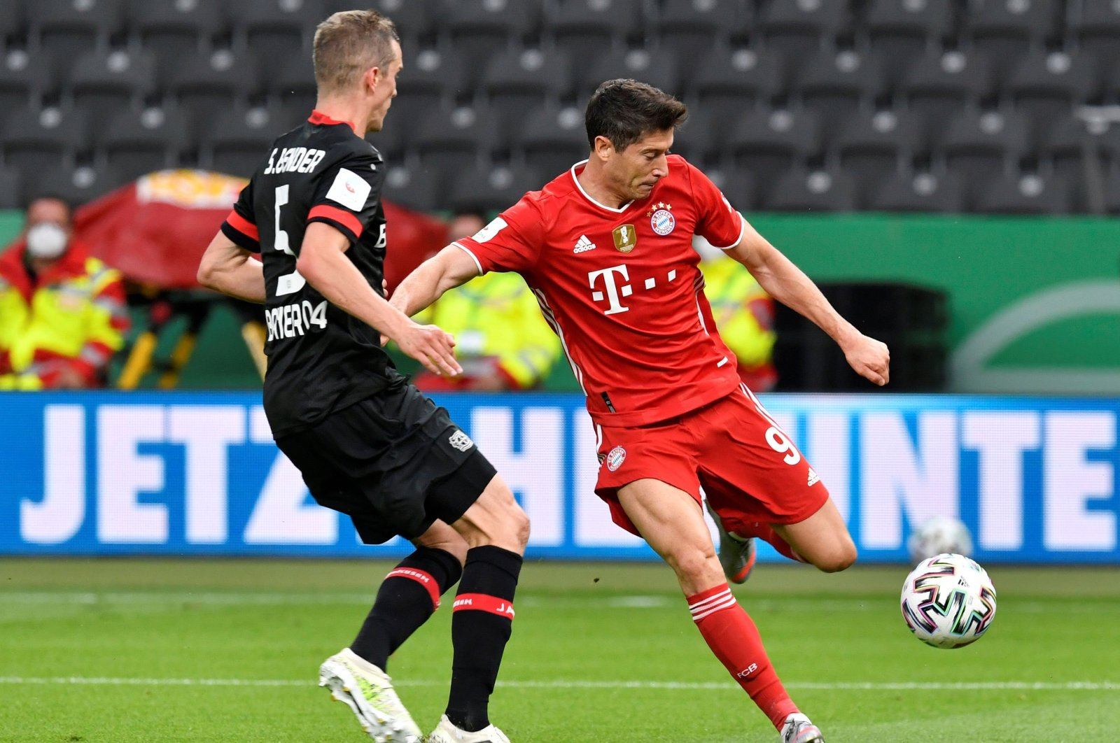 Bayern Munich's Robert Lewandowski (R) in action with Bayer Leverkusen's Sven Bender during a German Cup match at the Olympiastadion stadium in Berlin, Germany, July 4, 2020. (AP Photo)