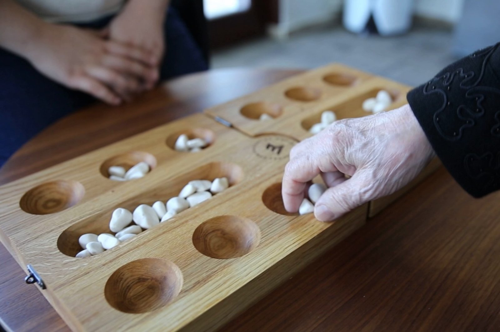 Two people play the traditional Turkish strategy and intelligence game Mangala.