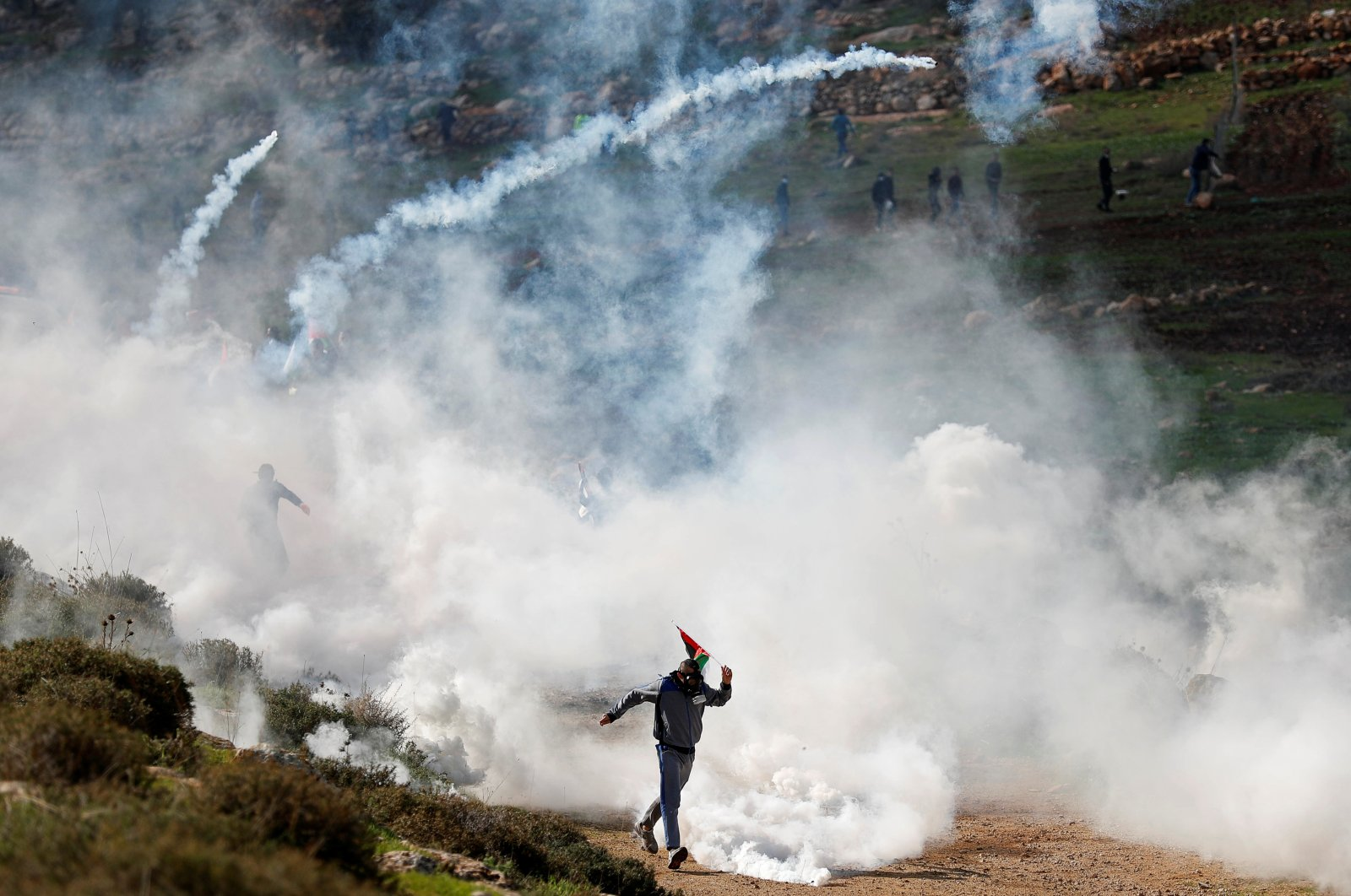 A Palestinian demonstrator runs away from tear gas canisters fired by Israeli forces during a protest against Jewish settlements, in Beit Dajan in the Israeli-occupied West Bank, Palestine, Dec. 18, 2020. (Reuters Photo)