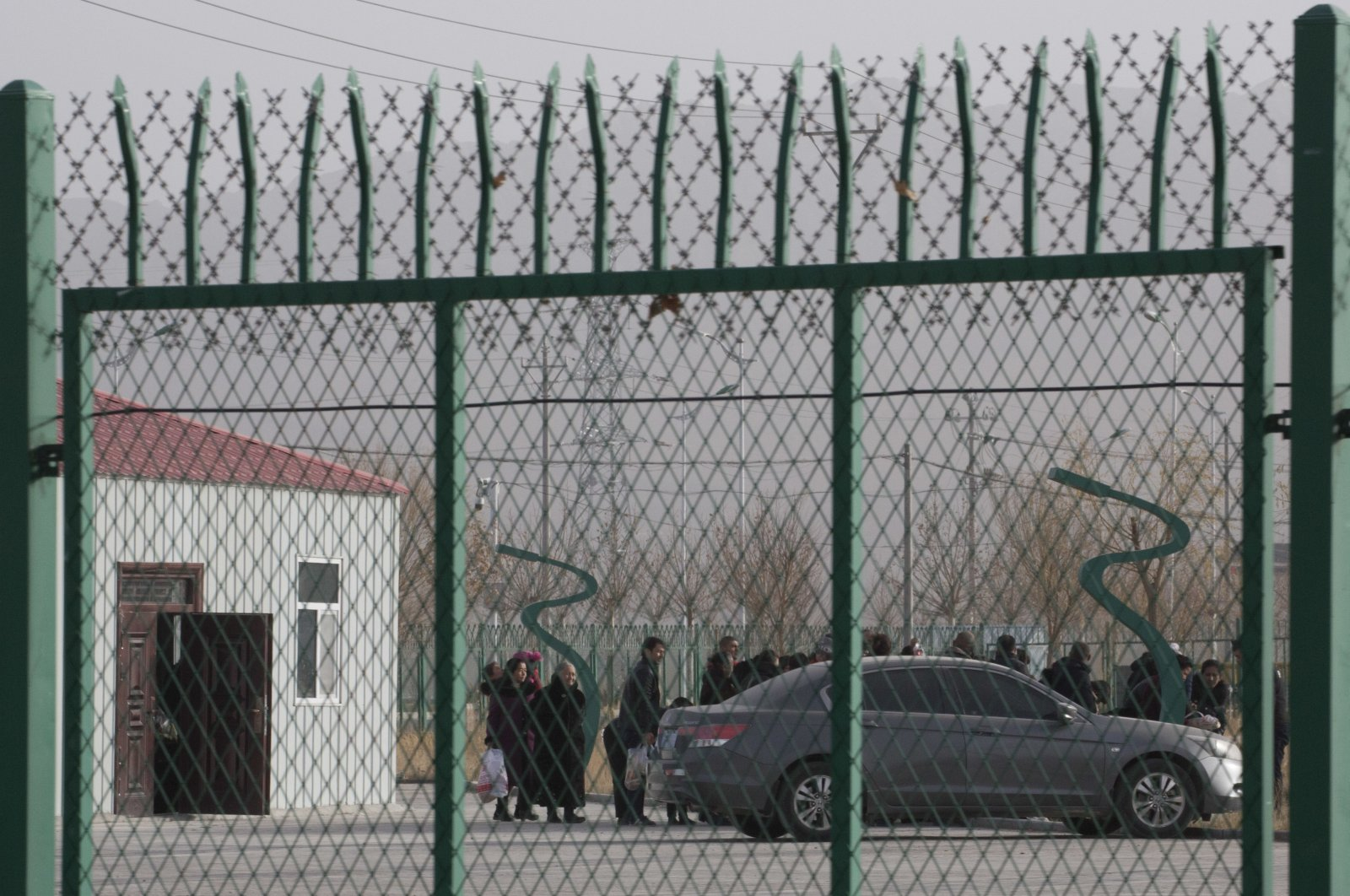 """People line up in an internment camp, called """"vocational skills education training service centers"""" by the Chinese government, in Artux, Xinjiang Uyghur Autonomous Region, western China, Dec. 3, 2018. (AP Photo)"""