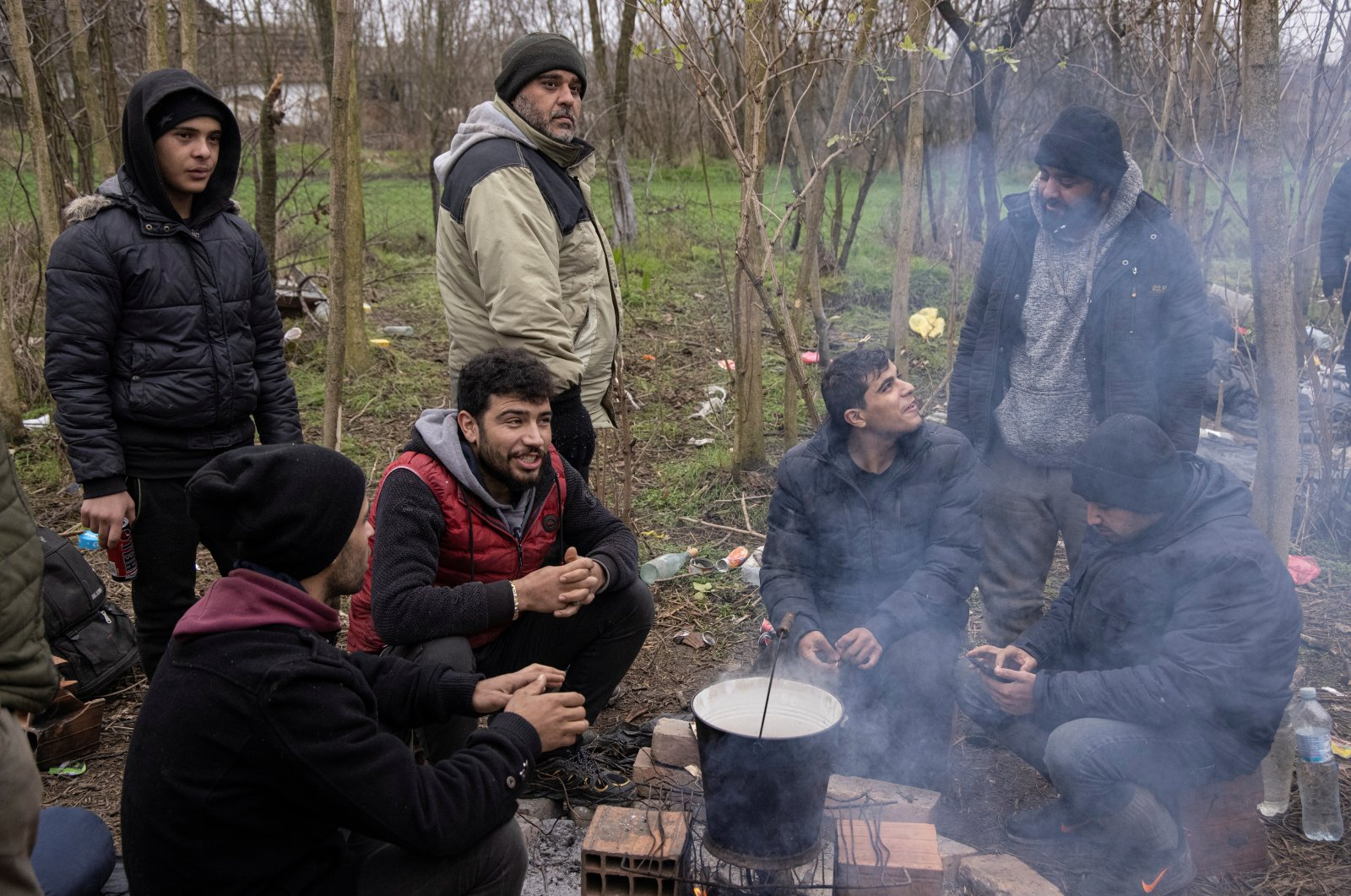 Migrants prepare food in front of an abandoned house close to the Serbia, Hungary and Romania border in the village of Majdan, Serbia, Dec. 16, 2020. (Reuters Photo)