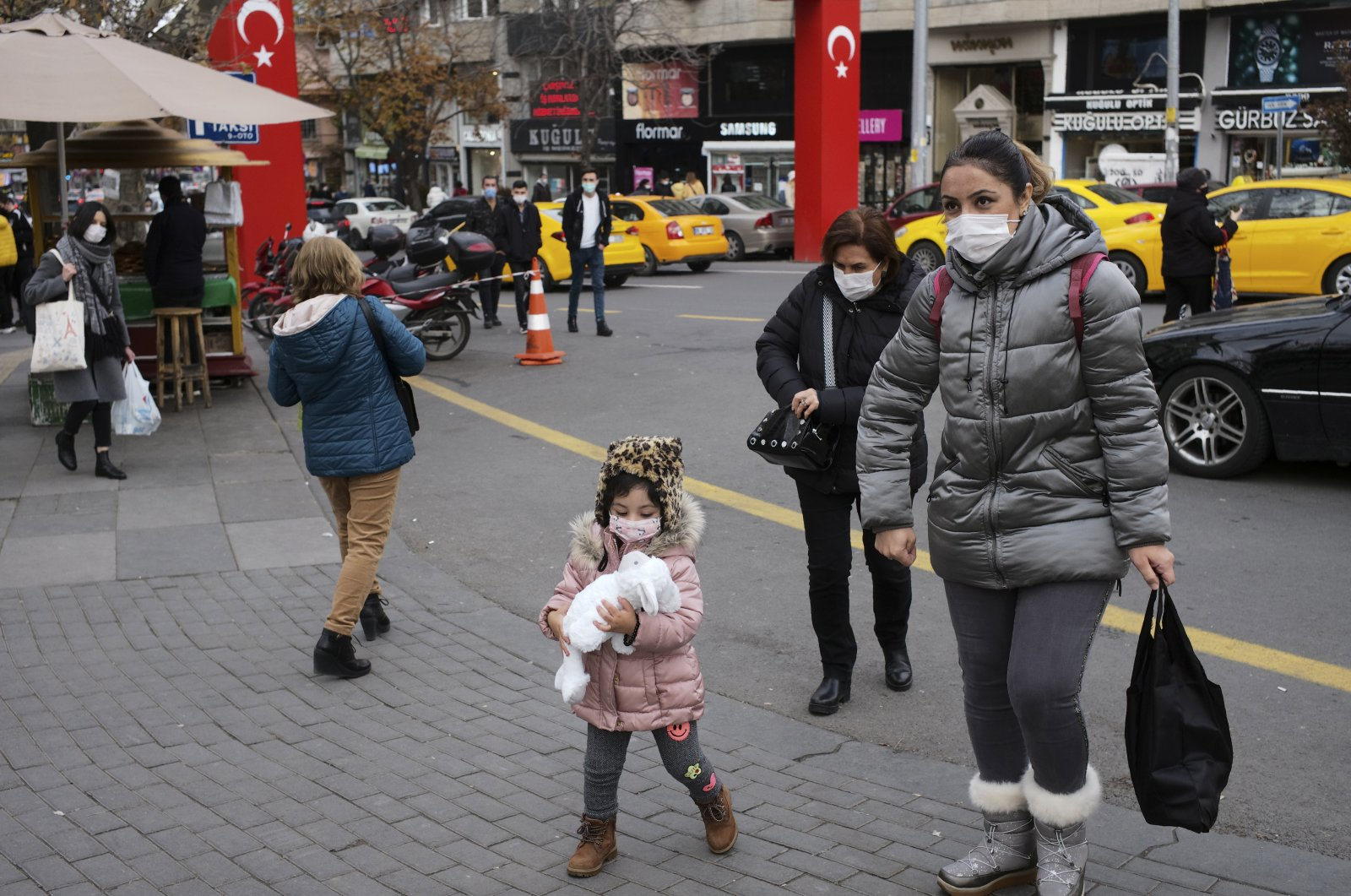 People wearing face masks to protect against coronavirus, walk along a street hours before a two-day weekend curfew, in Ankara, Turkey, Dec. 18, 2020. (AP Photo)