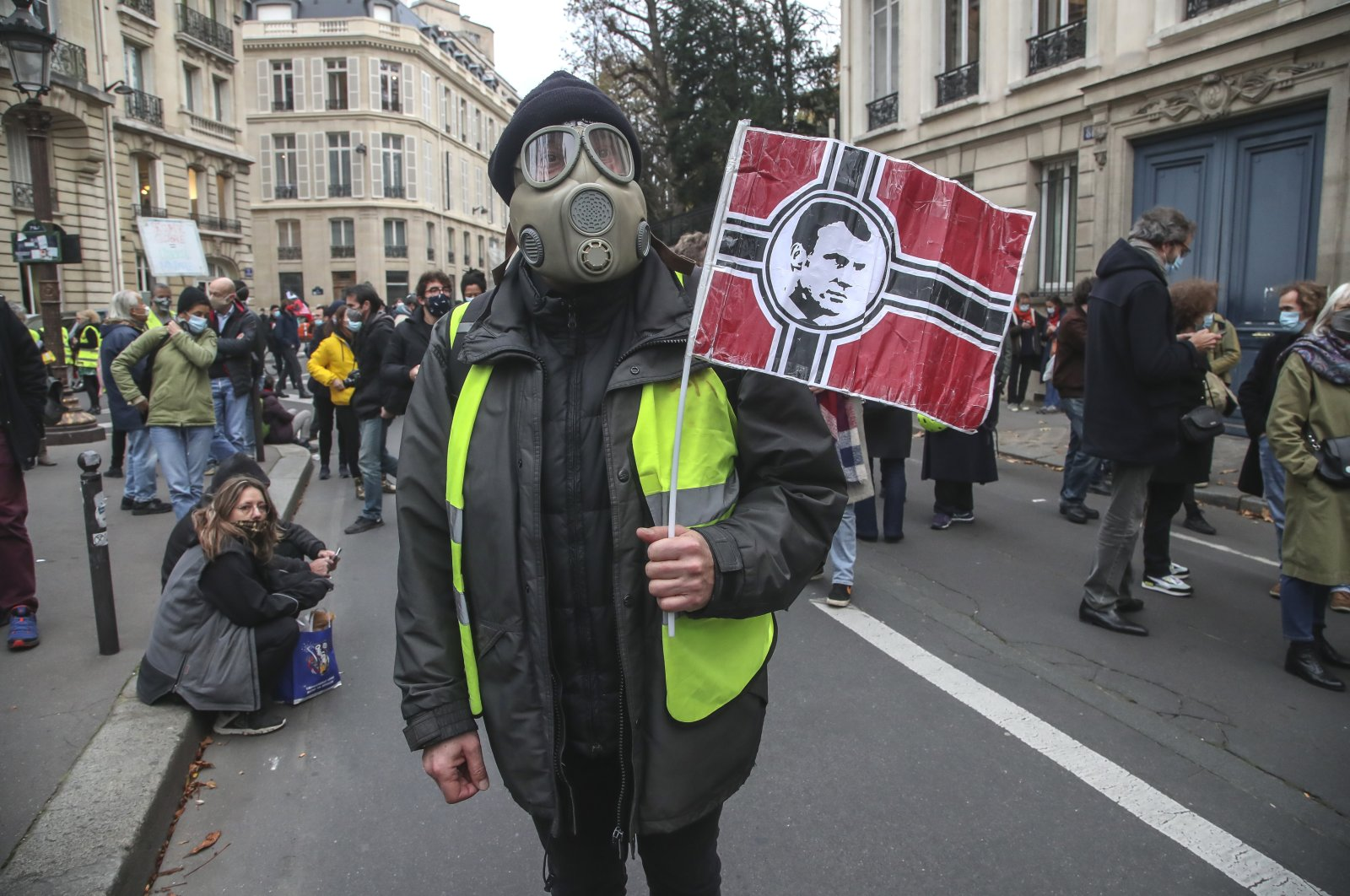 A demonstrator wearing a gas mask holds a banner representing the Nazi flag with the portrait of French President Emmanuel Macron on it during a protest by the National Assembly against the security bill in Paris, Nov. 17, 2020. (AP Photo)
