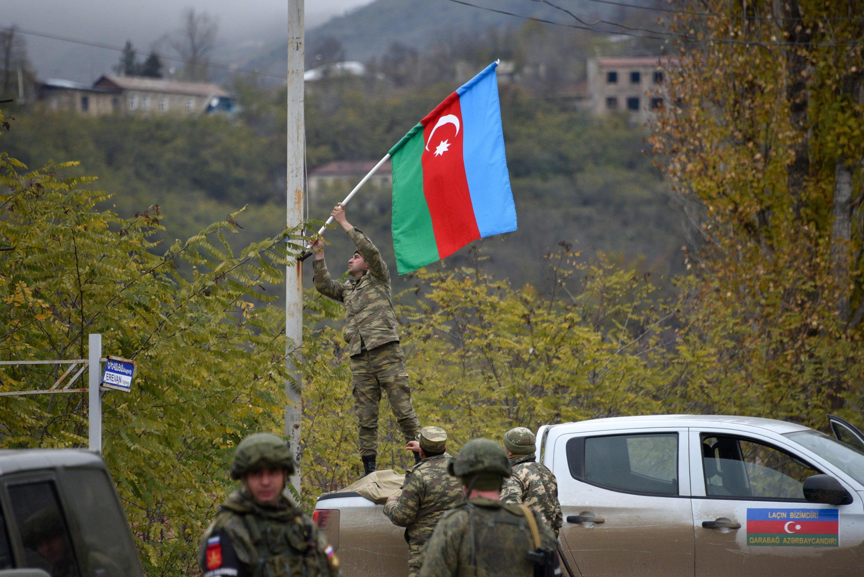 An Azerbaijani soldier fixes a national flag on a lamp post in the town of Lachin, Azerbaijan, Dec. 1, 2020. (Photo by Karen MINASYAN via AFP)