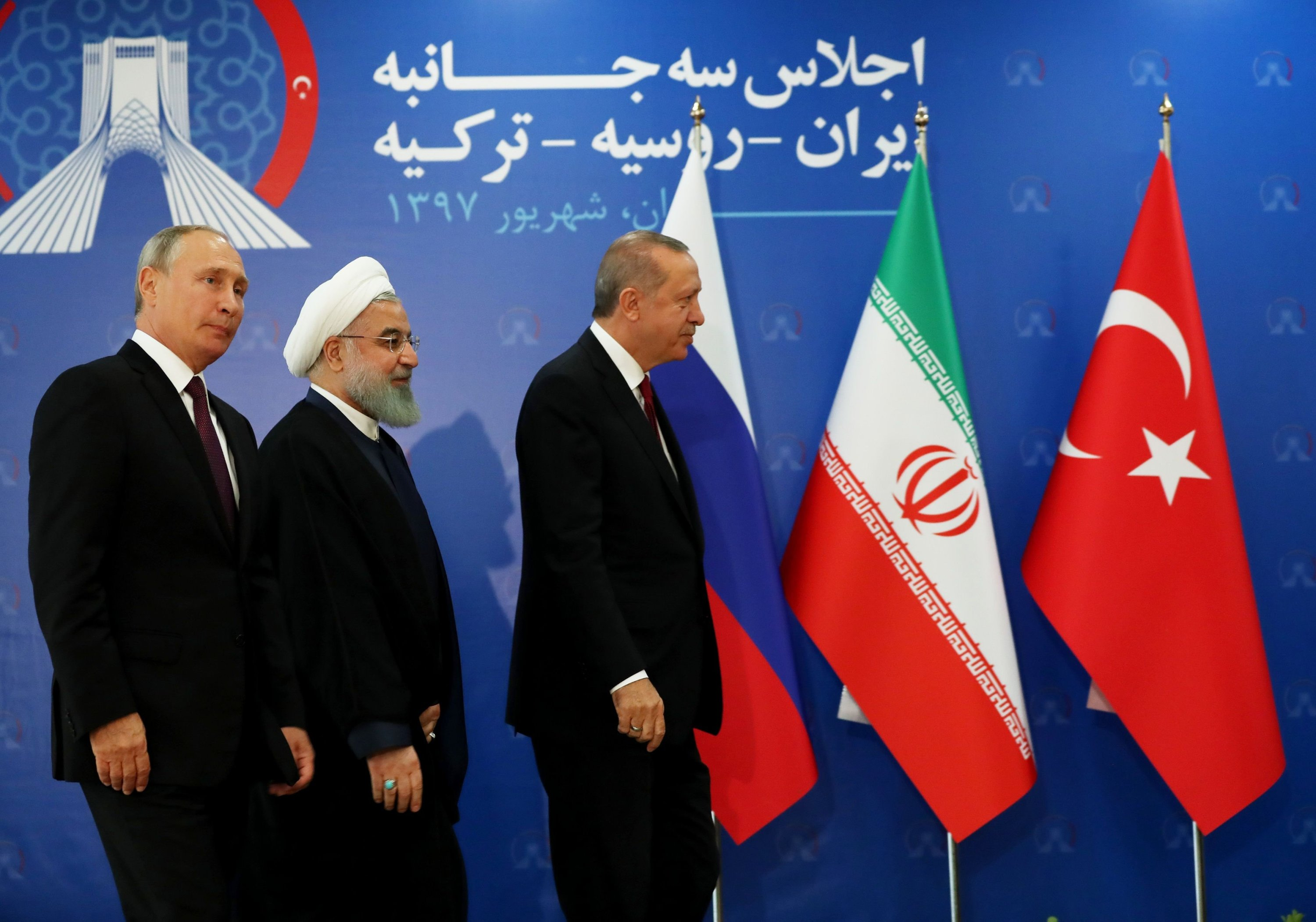 Russian President Vladimir Putin (L), Iranian President Hassan Rouhani (C) and President Recep Tayyip Erdoğan leave the stage during a trilateral summit in Tehran, Iran, Sept. 7, 2018. (HANDOUT PHOTO FROM TURKISH PRESIDENCY PRESS OFFICE via AFP)