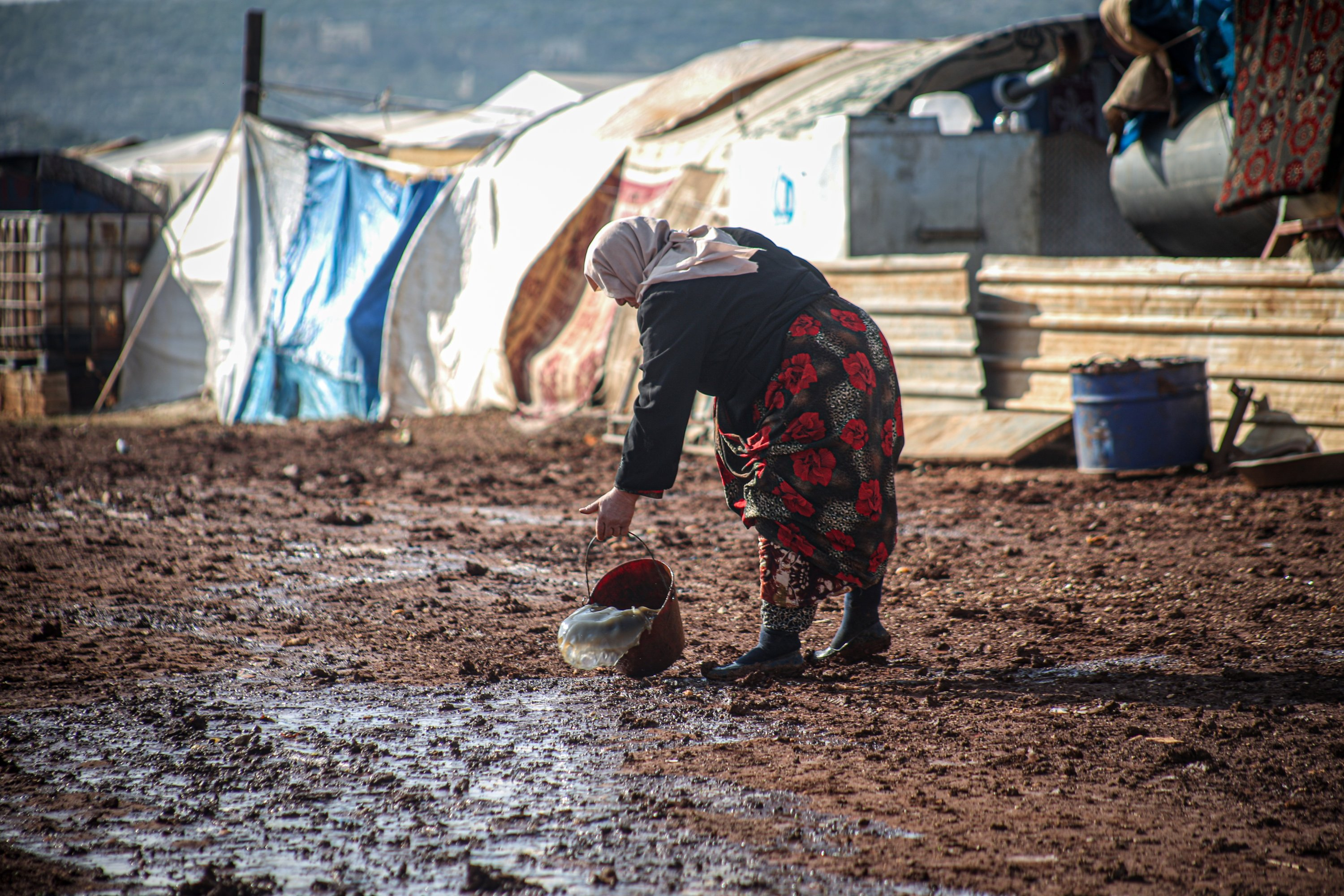 A woman tries to clear her tent of water as heavy rain floods Keferarouk refugee camp in northwestern Idlib, Syria, Dec.19, 2020. (AA)