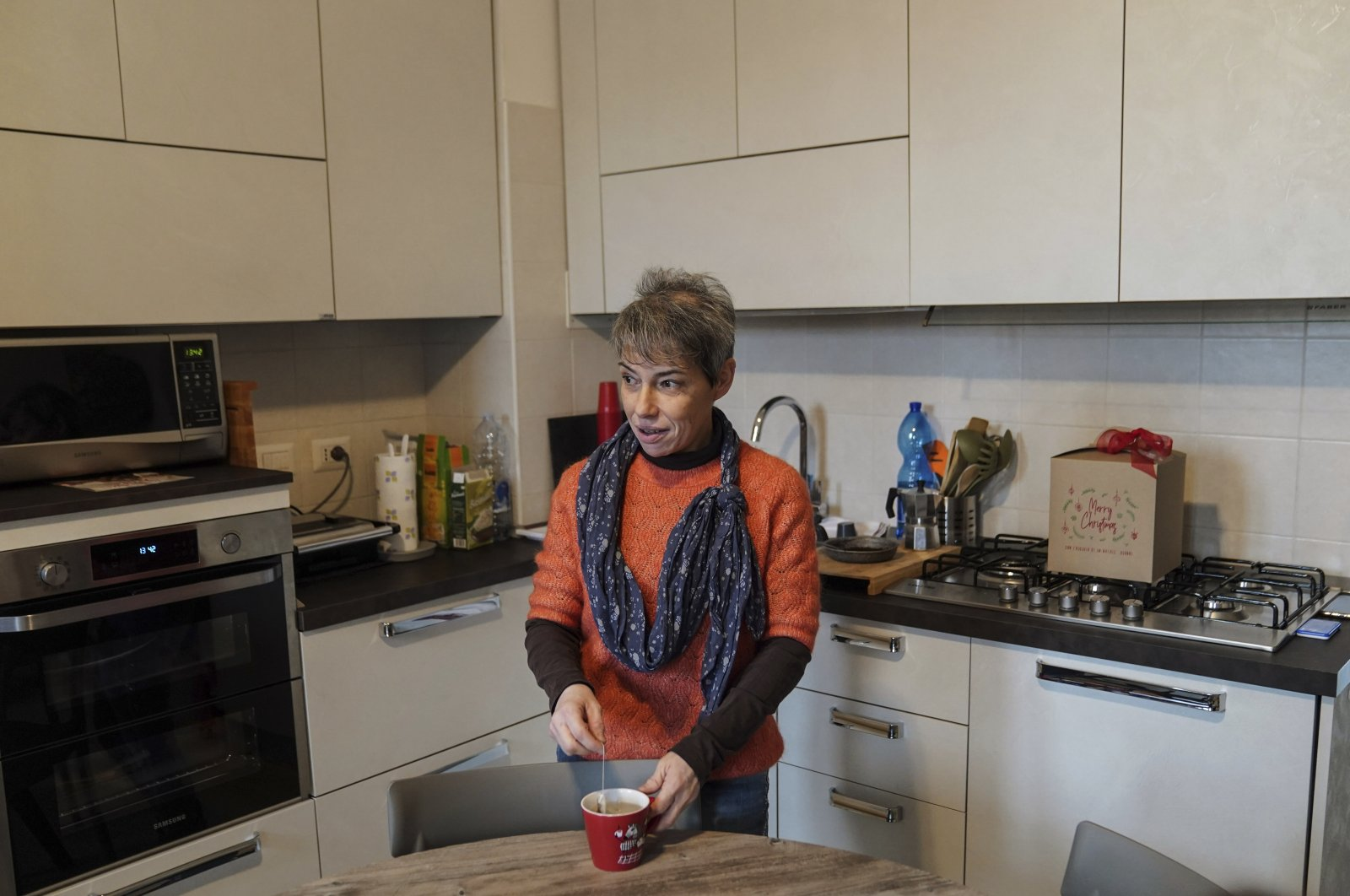 Elena Simone prepares an herbal tea in her kitchen at her house in Novate Milanese, Italy, Dec. 11, 2020. (AP Photo)