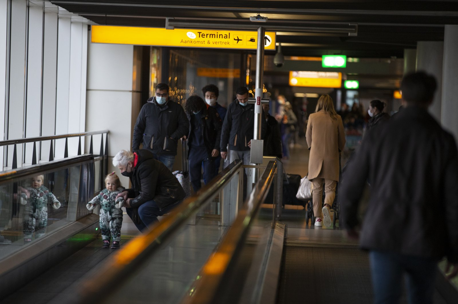 Arriving and departing passengers use moving walkways at Schiphol Airport, near Amsterdam, Netherlands, Dec. 18, 2020. (AP Photo)