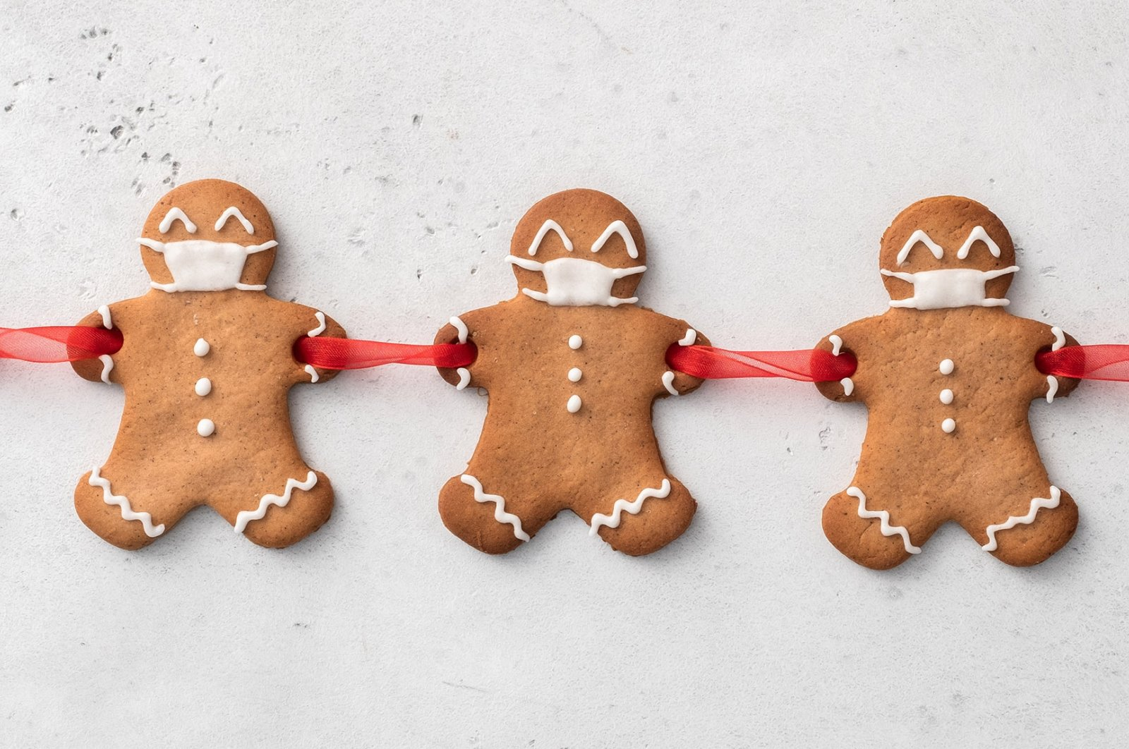 Cut out holes in your gingerbread men's hands before cooking to join them together with a ribbon and add icing masks. (Shutterstock Photo)