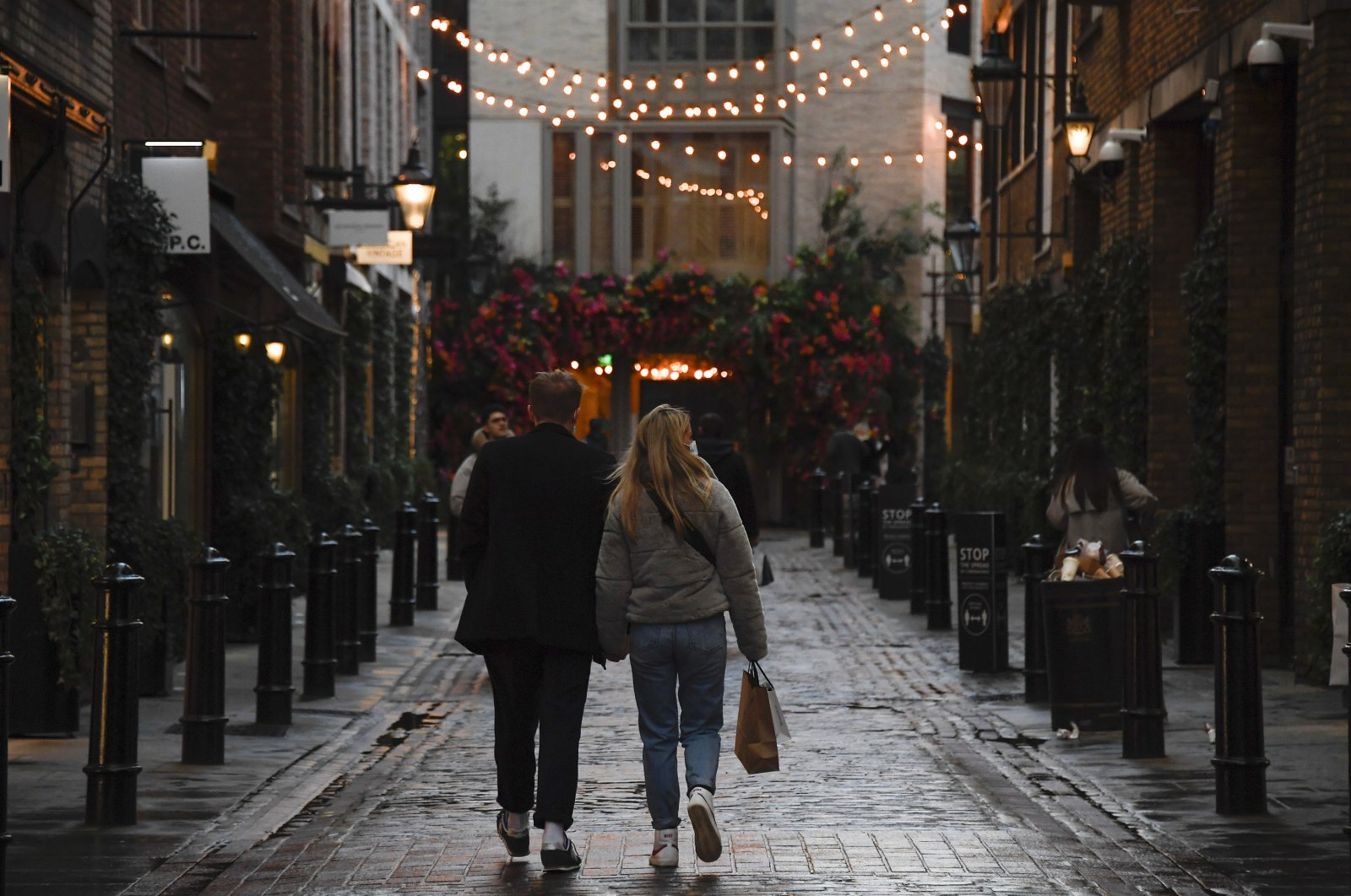 A couple holds hands as they walk in Covent Garden, ahead of the new Tier-4 restriction measures, in London, England, Dec. 19, 2020. (AP Photo)